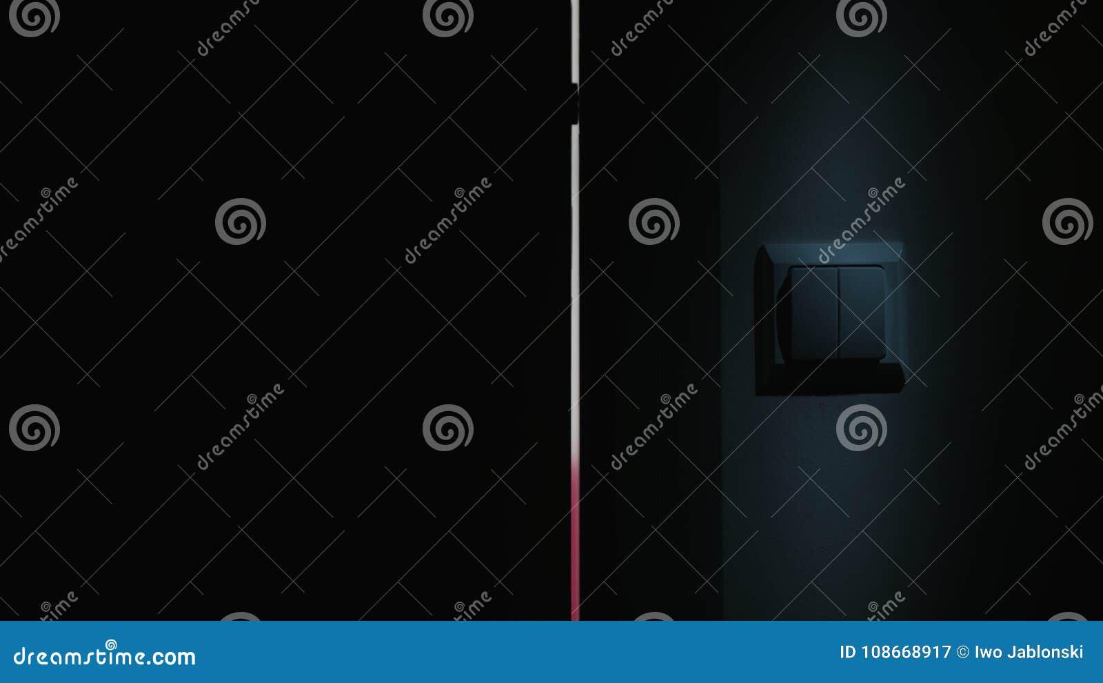 Um interruptor da mão na luz em uma sala escura