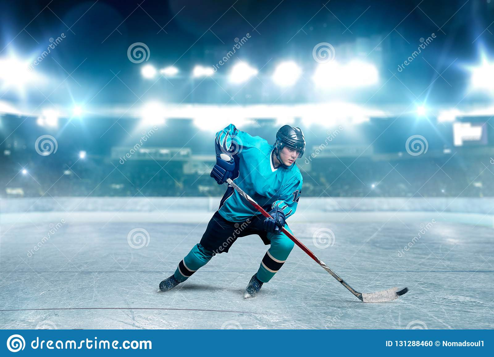 Um jogador de hóquei que patina com a vara na arena do gelo