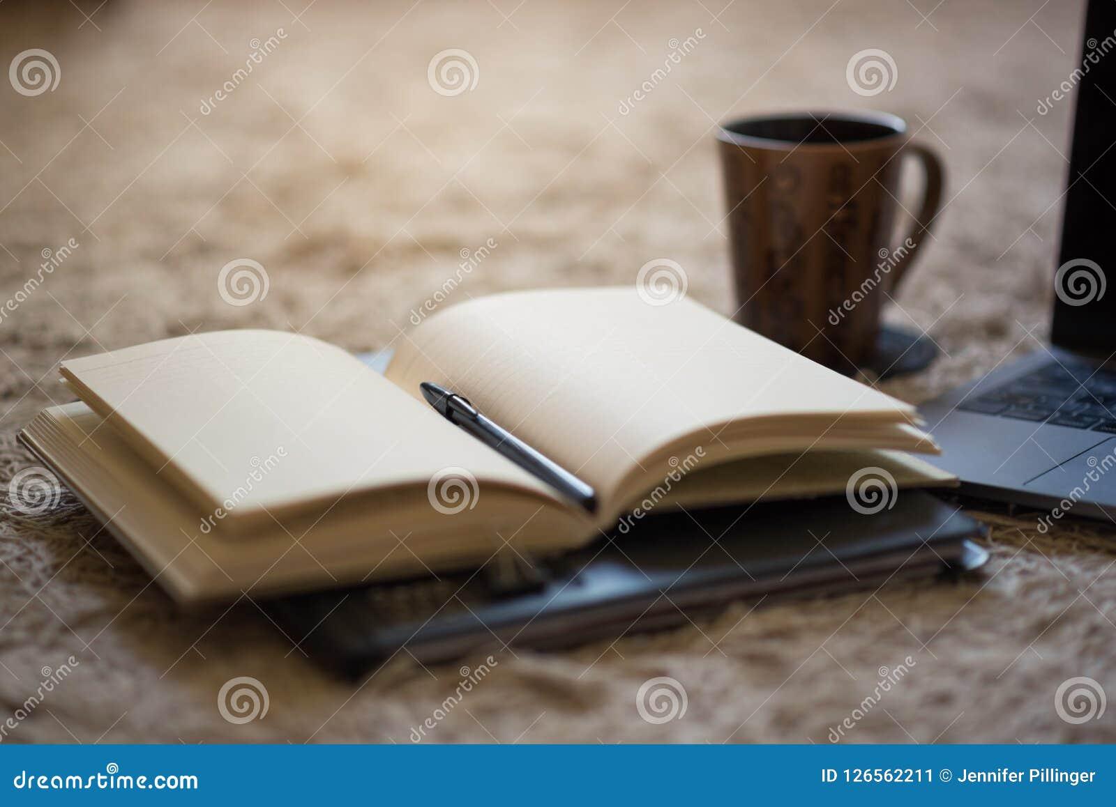 Um jornal aberto com pena e as páginas vazias illuminating claras mornas