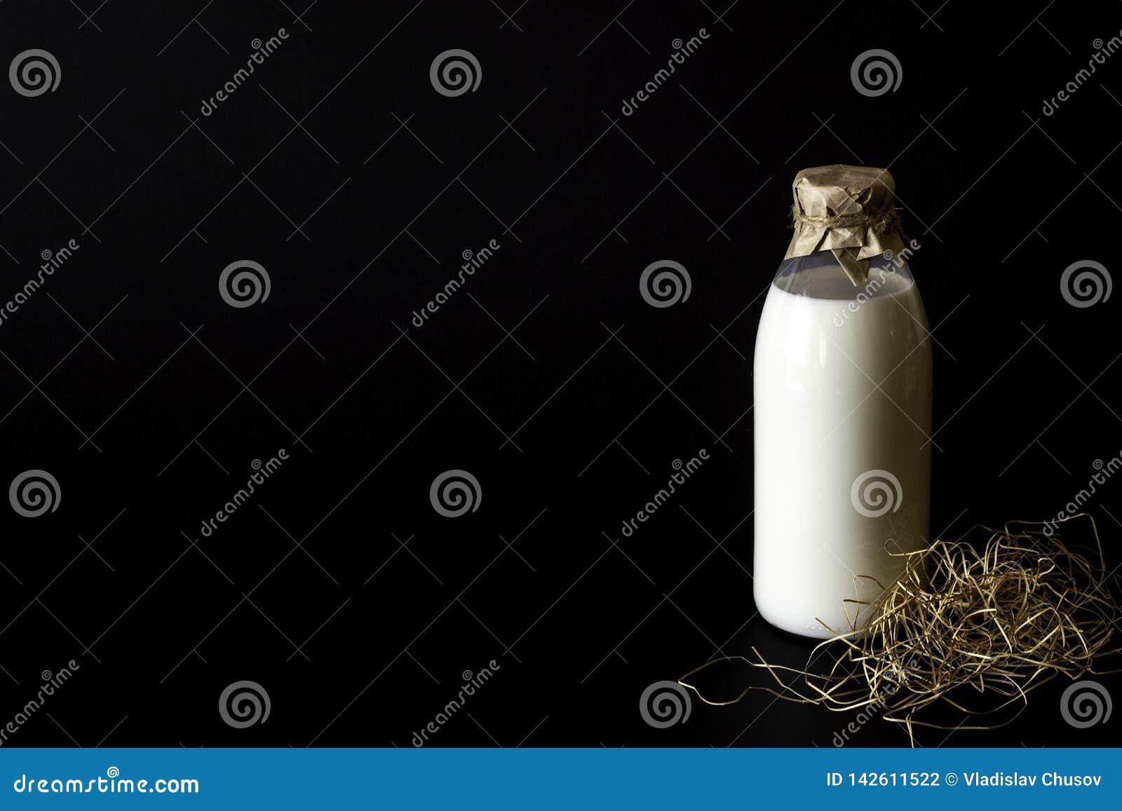 Um leite da garrafa em um fundo preto