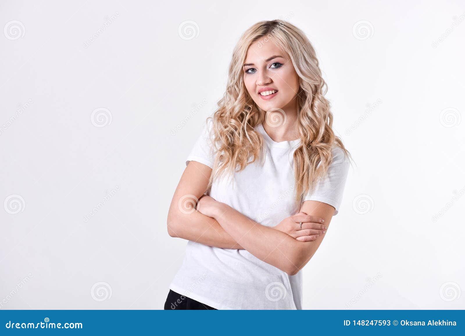 Um louro bonito novo da menina está com mãos dobradas, uma camisa branca, em um fundo branco