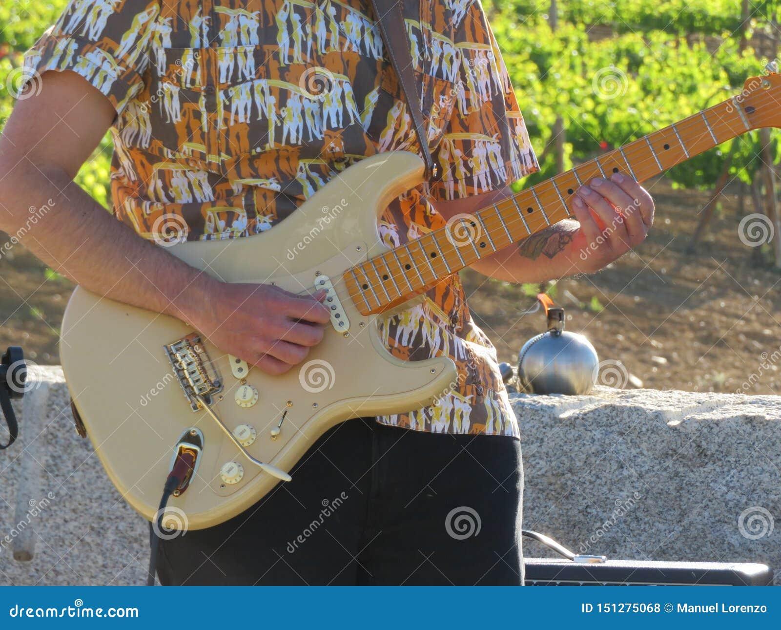 Um músico que joga a guitarra que compõe músicas bonitas