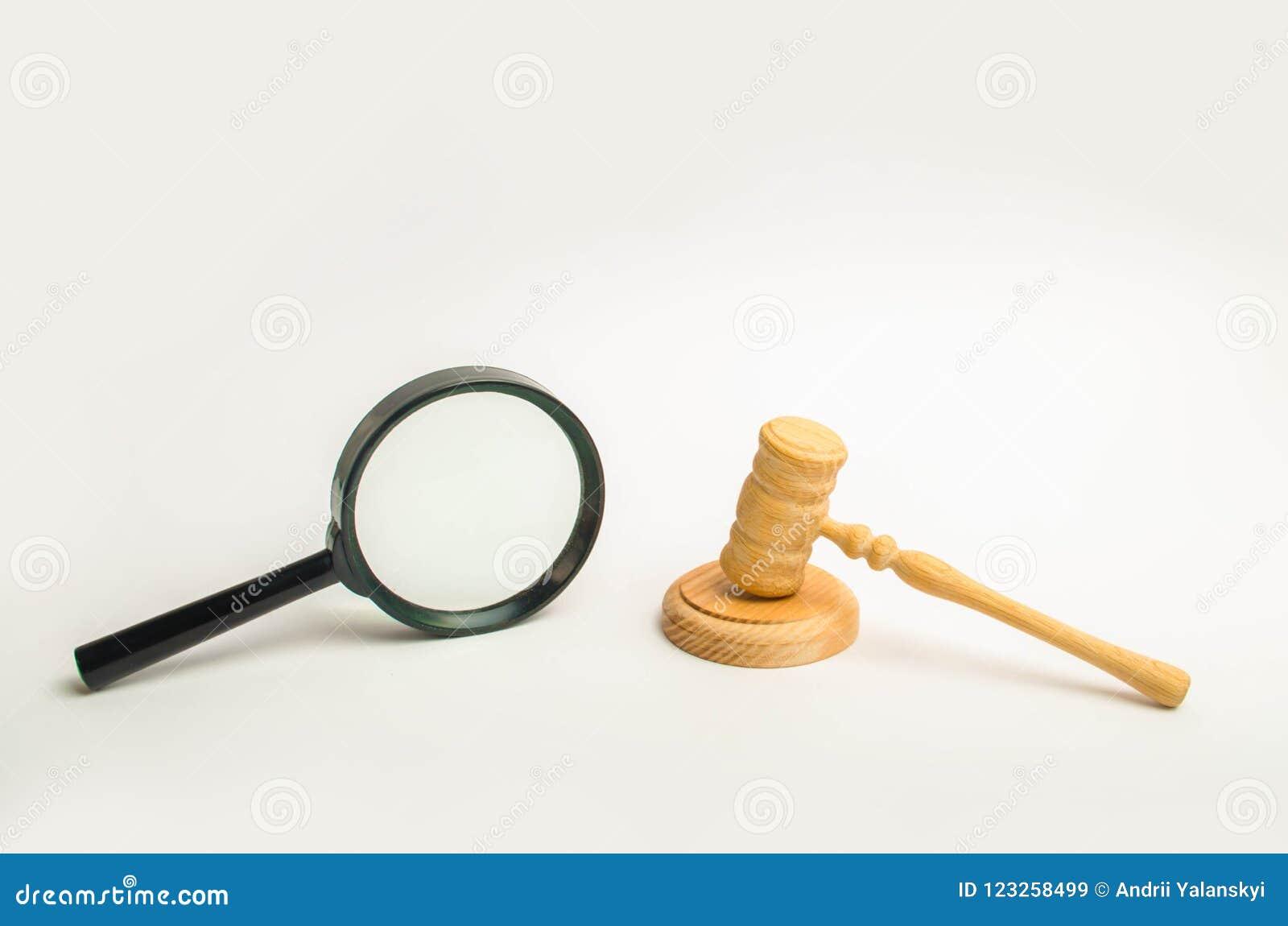 Um martelo do ` s do juiz e uma lente de aumento em um fundo branco Conhecimento com o exemplo, a pesquisa e a avaliação judiciai