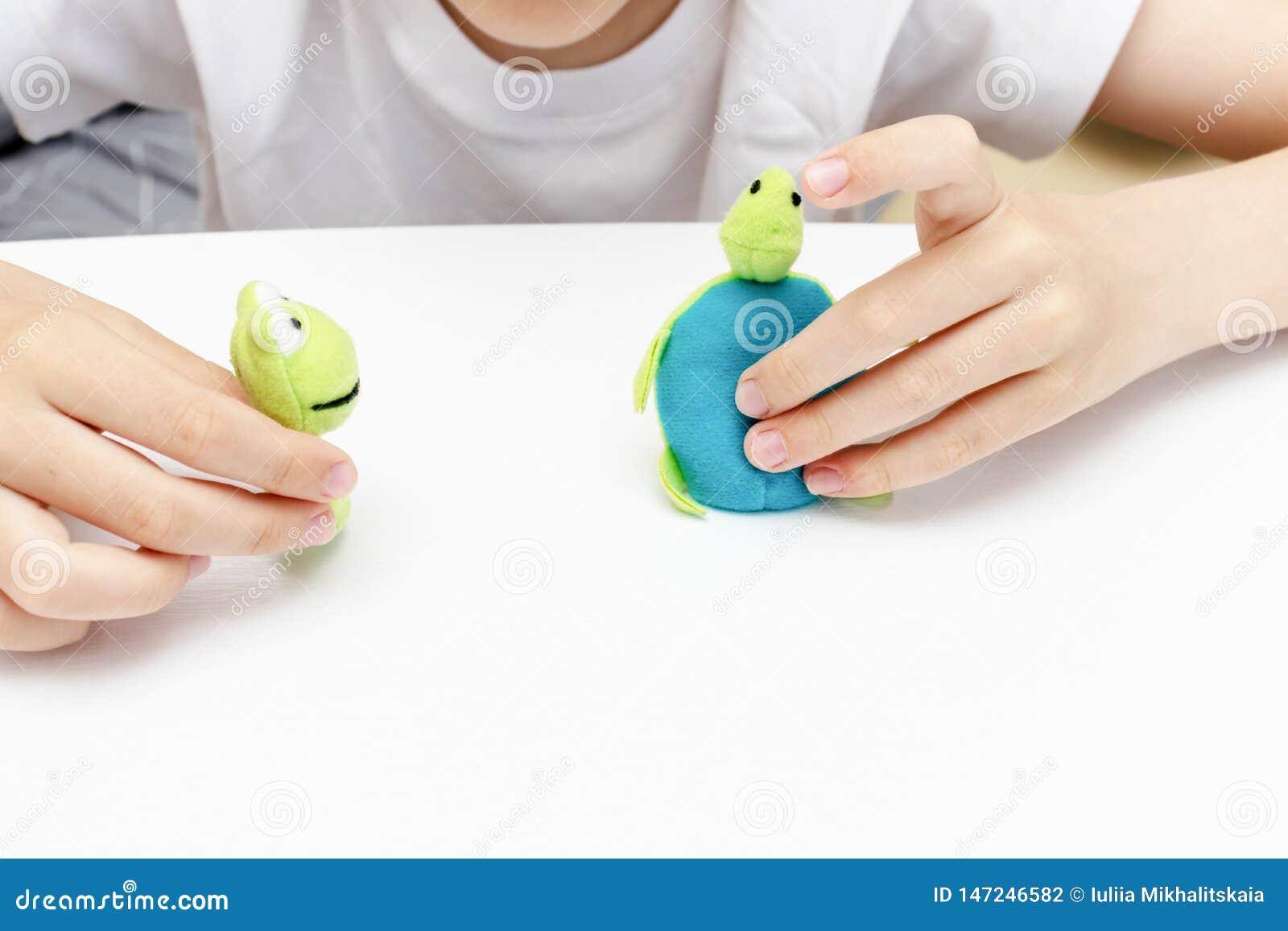 Um menino caucasiano que joga pap?is diferentes usando fantoches do dedo, brinquedos para expressar suas emo??es, agress?o, medo