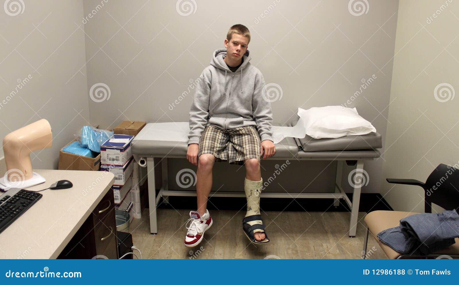 Um menino com muletas senta-se, esperando o doutor