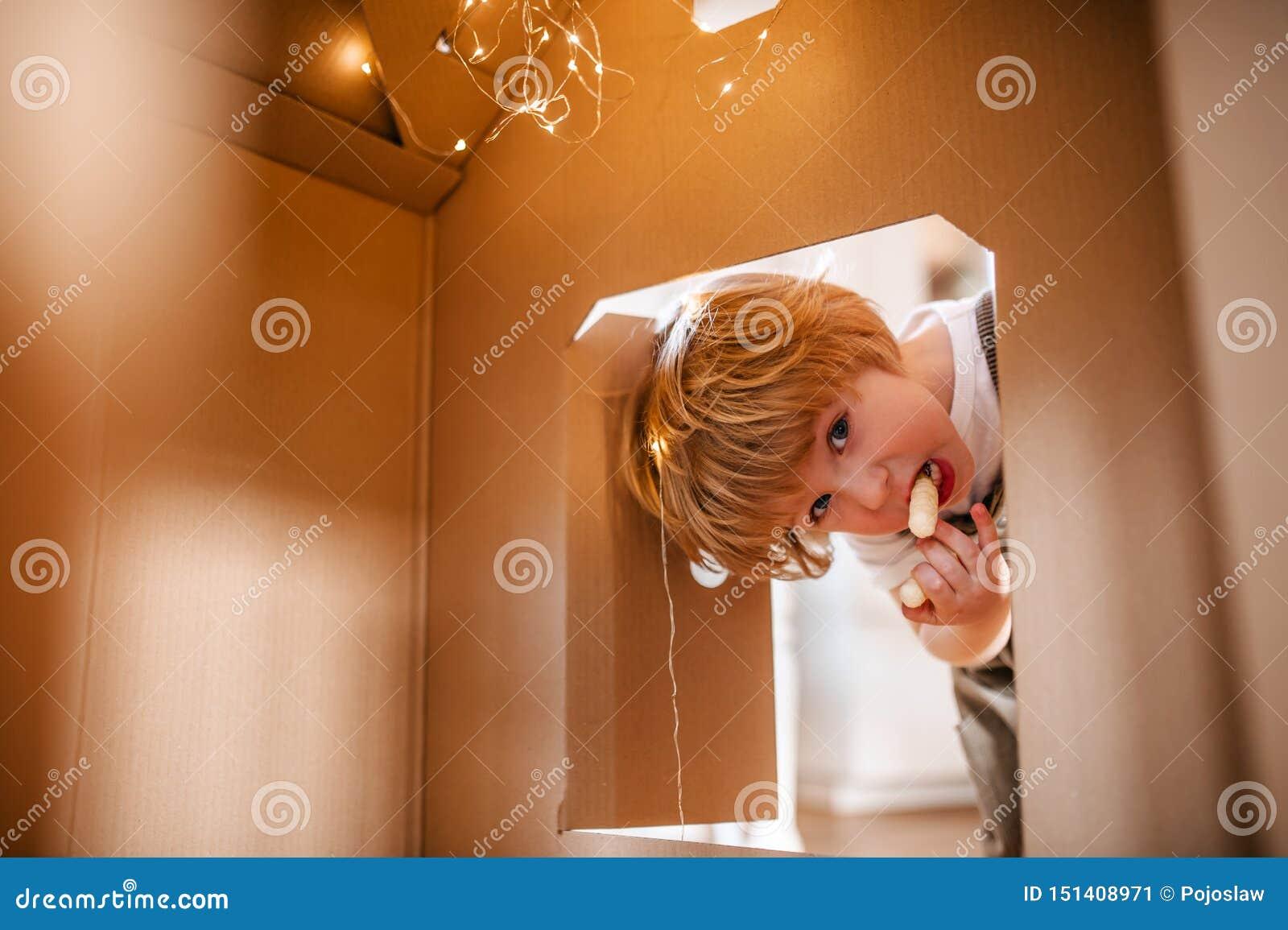 Um menino da crian?a que joga com uma casa do papel da caixa dentro em casa