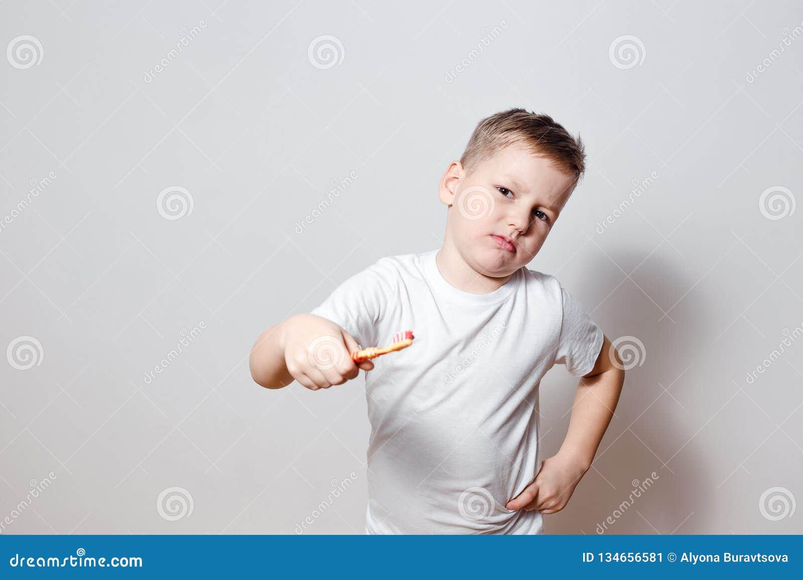 Um menino em um t-shirt branco não quer escovar seus dentes