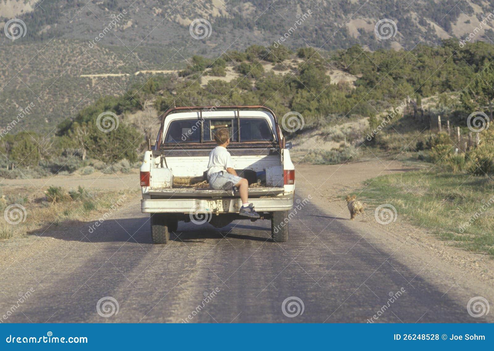 Um menino na parte traseira de uma camionete