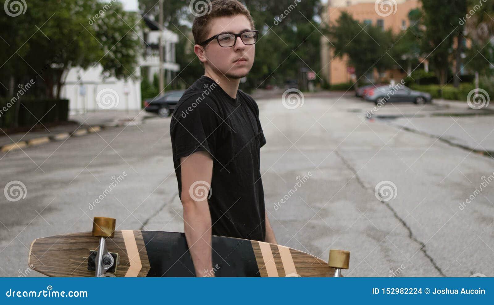 Um menino novo guarda seu skate