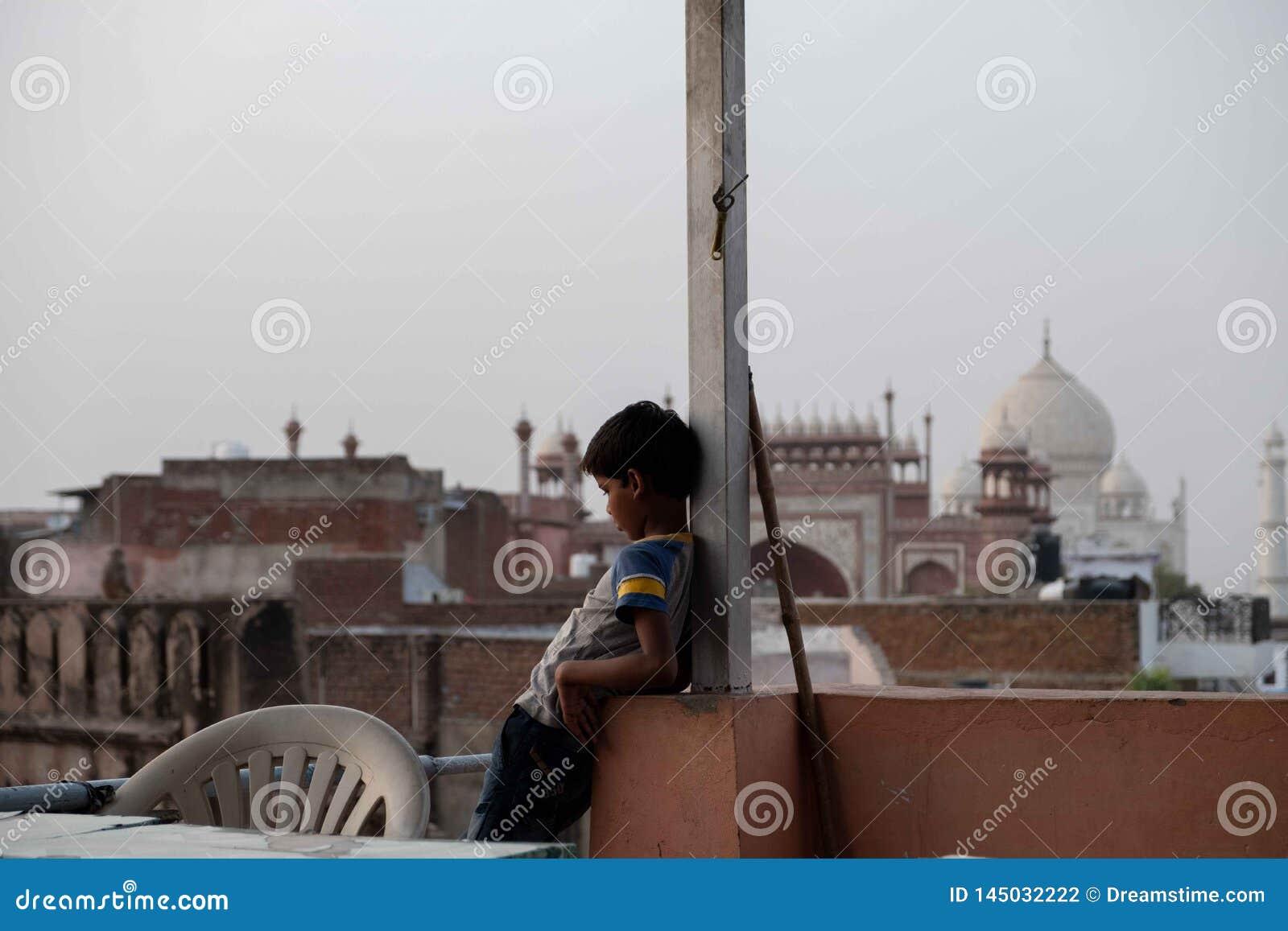 Um menino olha um papagaio que está sendo voado com Taj Mahal no fundo