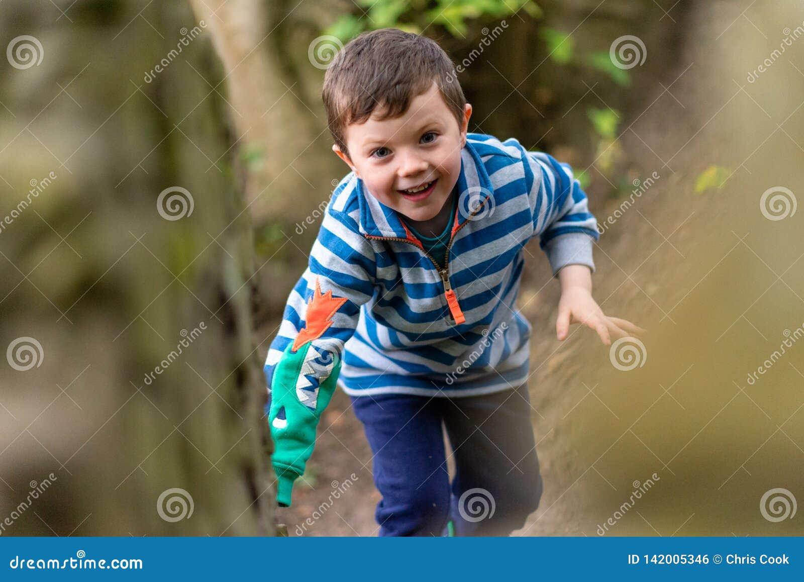 Um menino pequeno na roupa brilhante escala através de uma floresta enquanto sorrindo