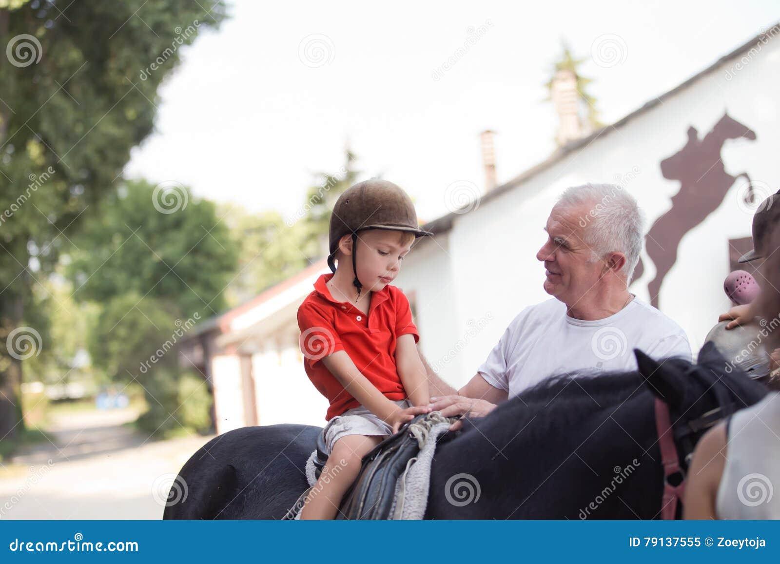 Um menino que senta-se sobre um cavalo preto que escuta seu grandfather& x27; instrução de s