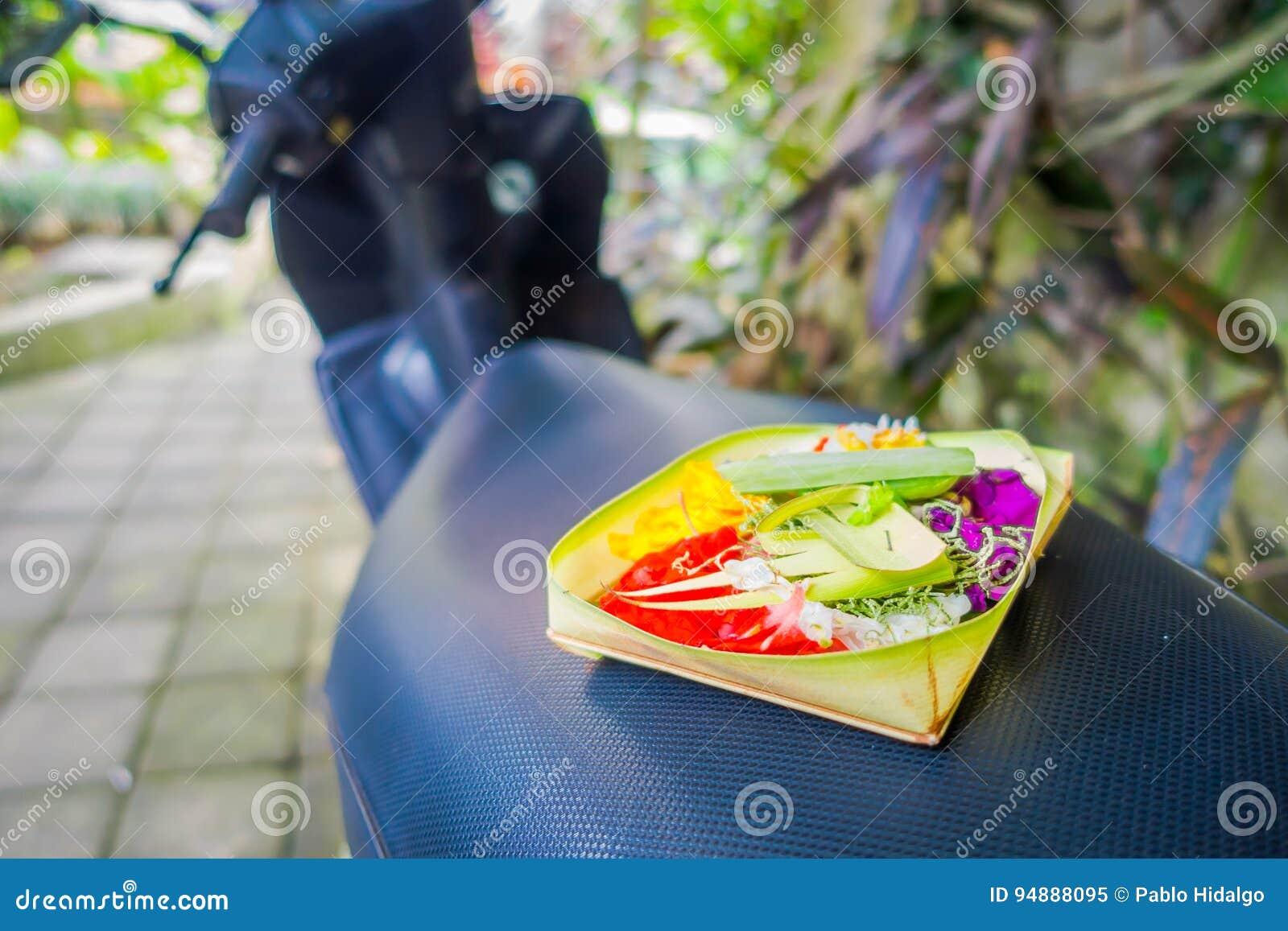 Um mercado com uma caixa feita das folhas, dentro de um arranjo das flores em um motorcyle, na cidade de Denpasar em Indonésia