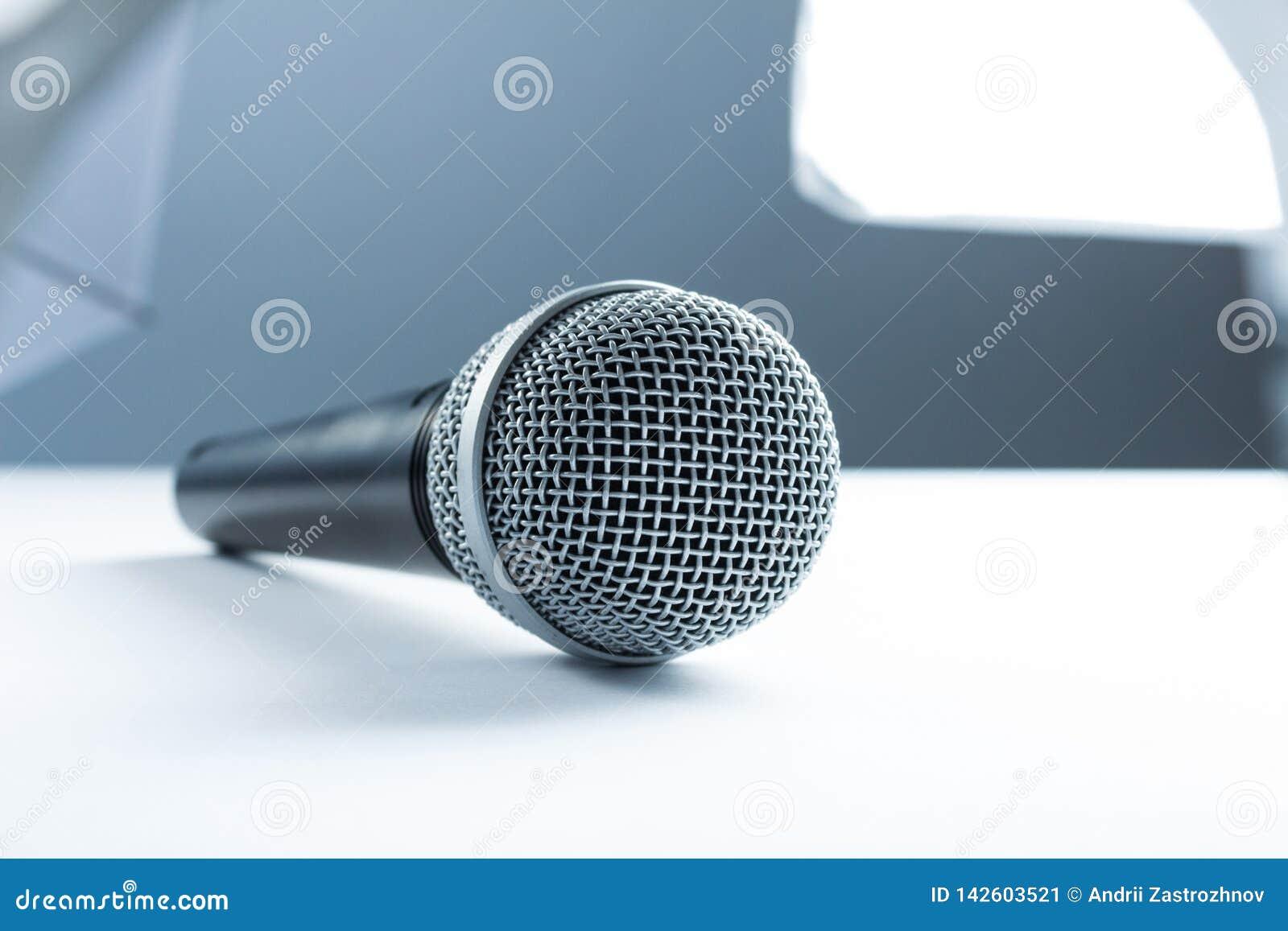 Um microfone que encontra-se em uma tabela branca Na perspectiva do equipamento do estúdio, iluminação
