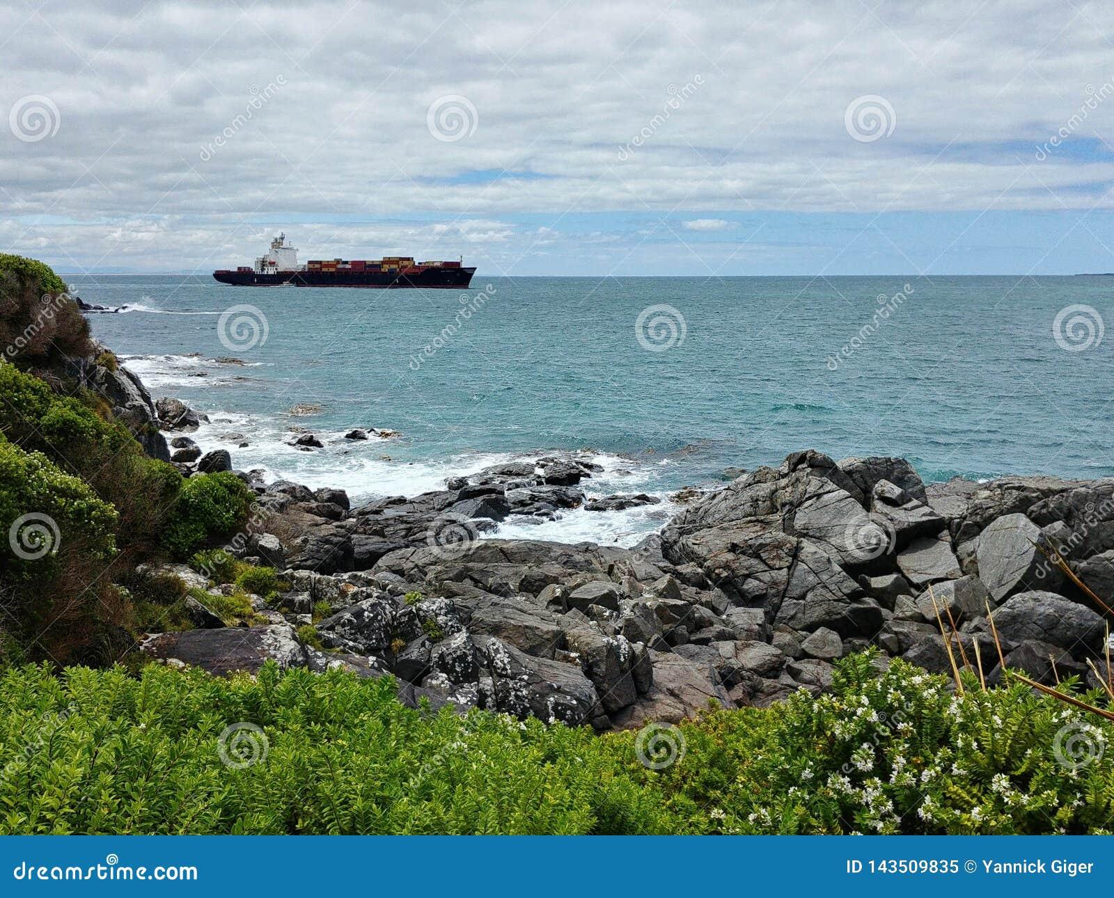 Um navio de recipiente está saindo do porto do blefe, Nova Zelândia