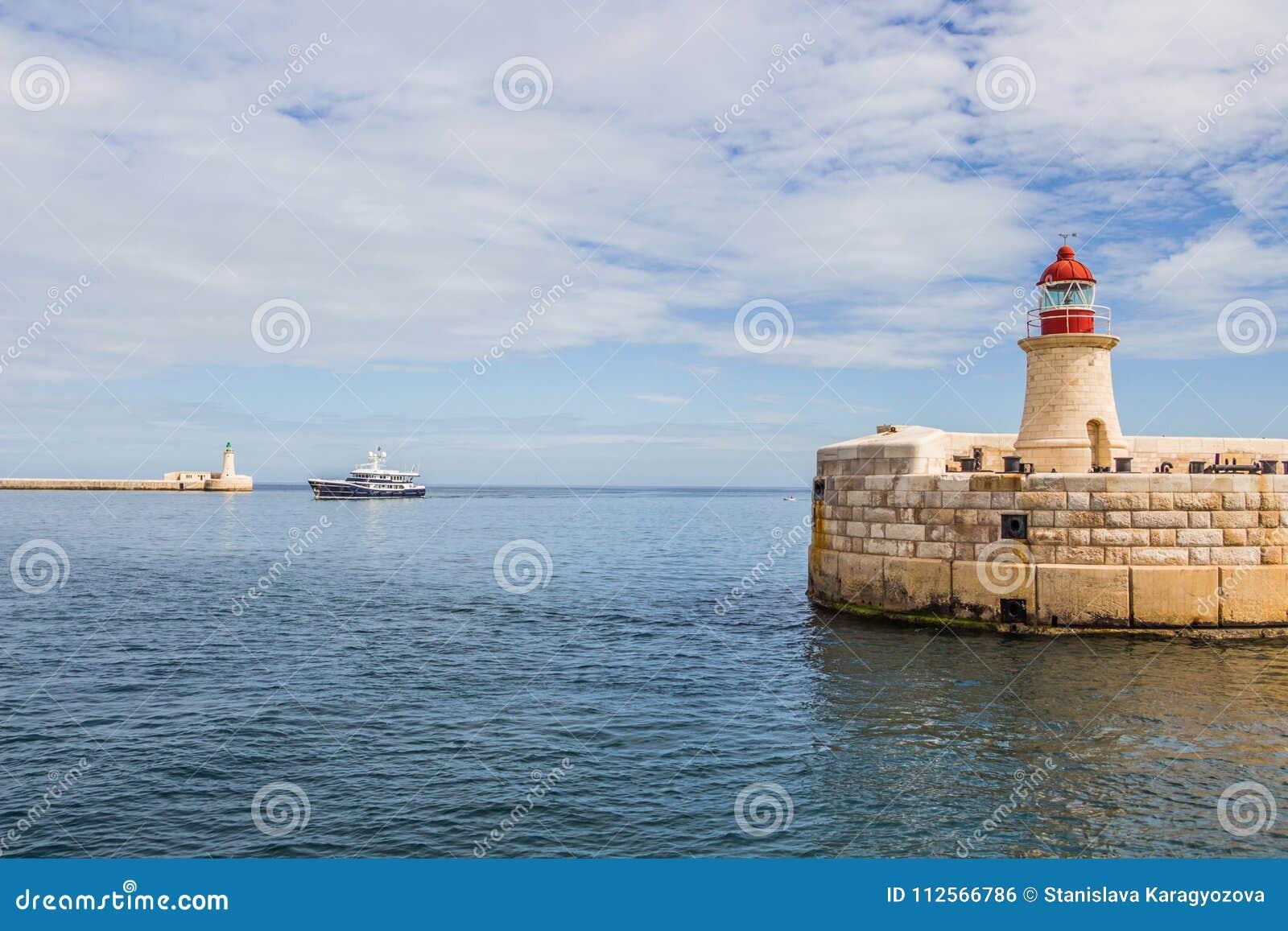Um navio entre a luz do quebra-mar de Ricasoli e o St Elmo Breakwater Head Light, Valletta, Malta