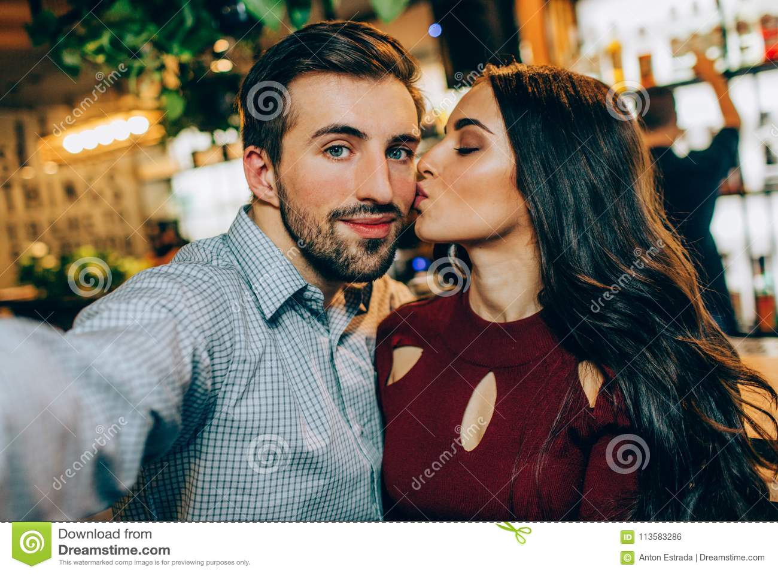 Um outro selfie dos pares A menina está beijando seu sócio quando tomar uma imagem Olham felizes junto
