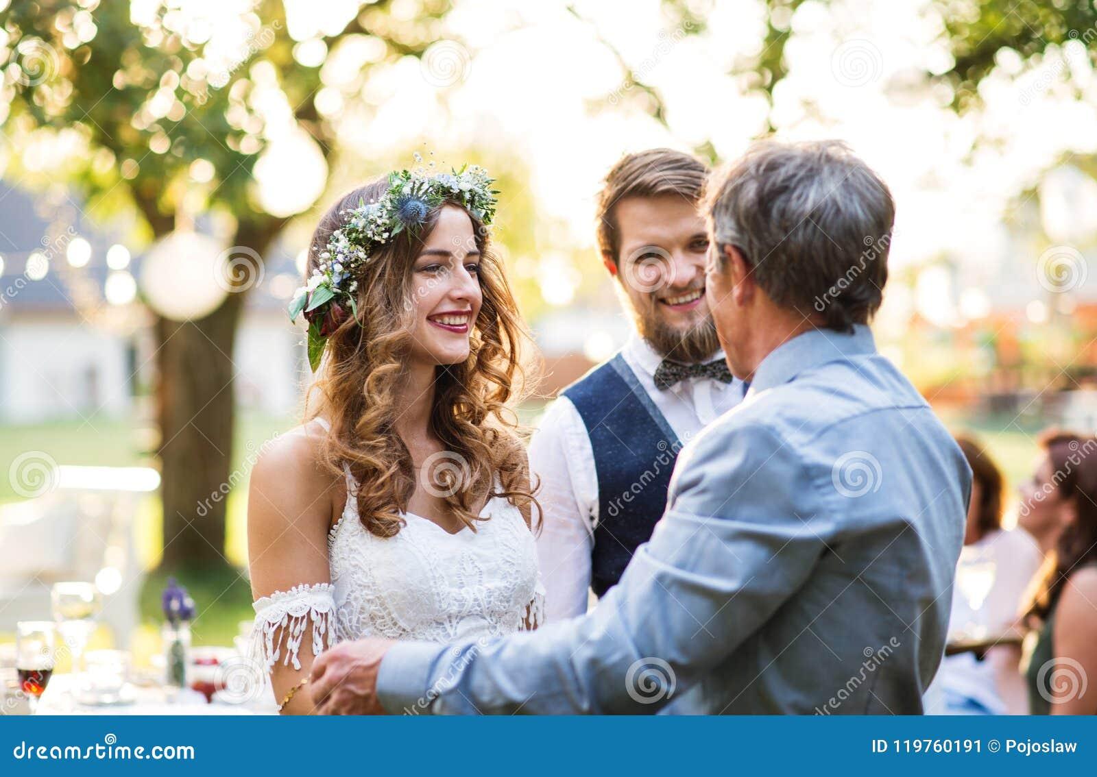 Um pai que felicita noivos no copo de água no quintal