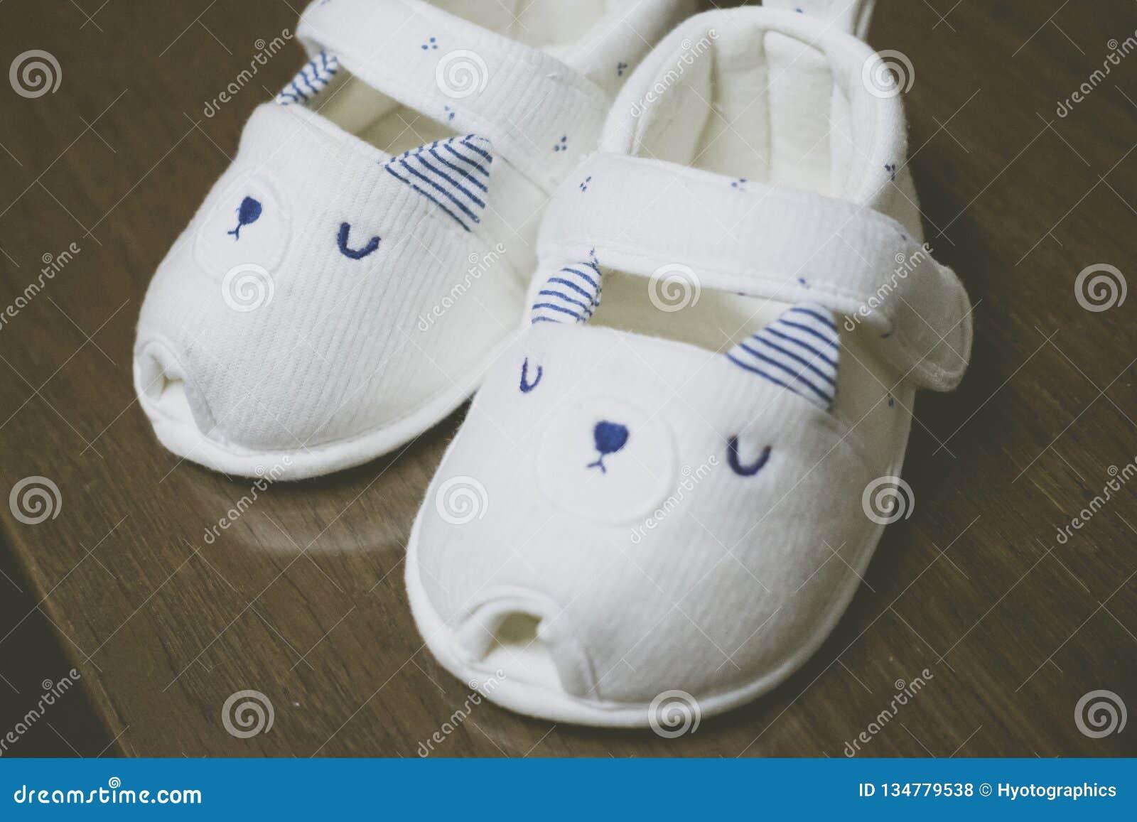 Um par das sapatas de bebê brancas na tabela de madeira
