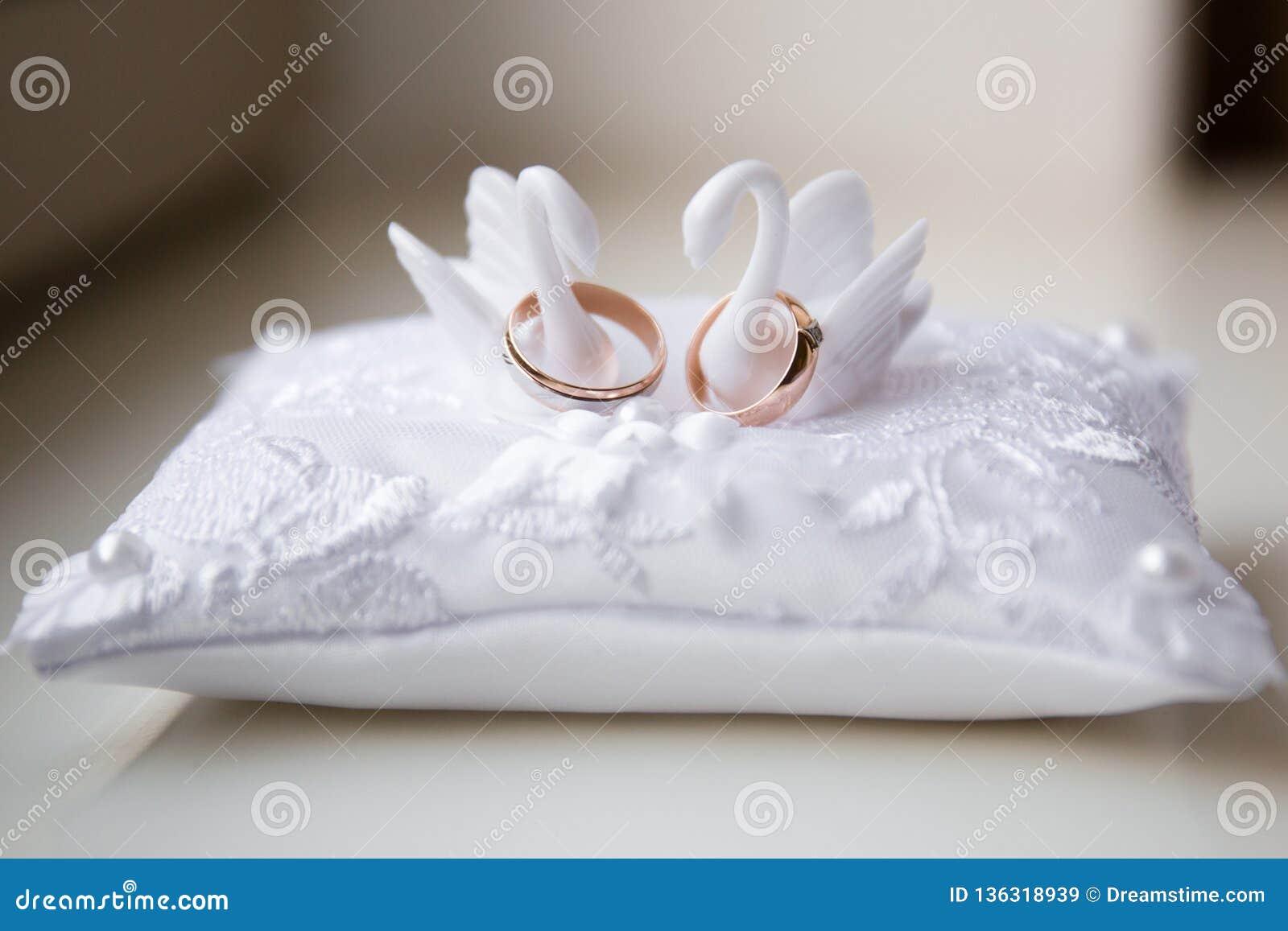 Um par de alianças de casamento em um descanso branco
