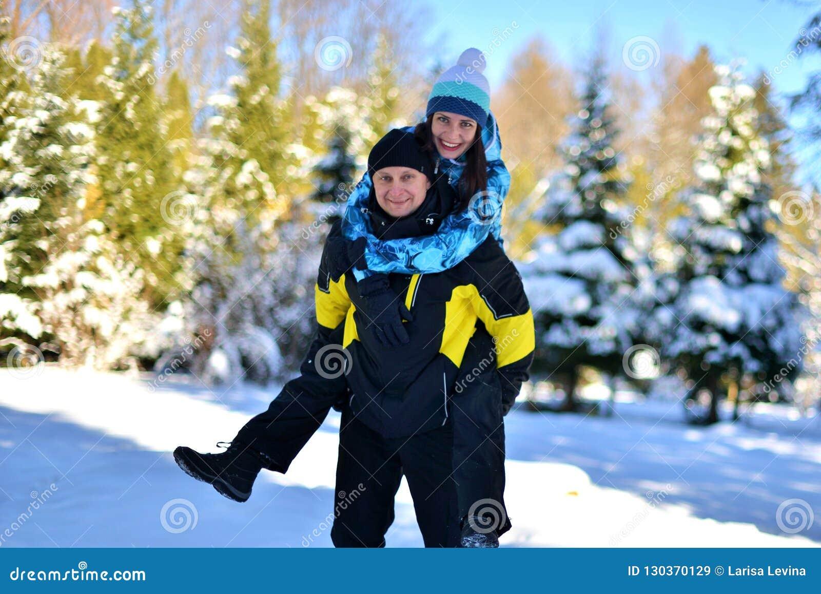 Um par de amor casado que engana ao redor em uma floresta nevado em um inverno ensolarado