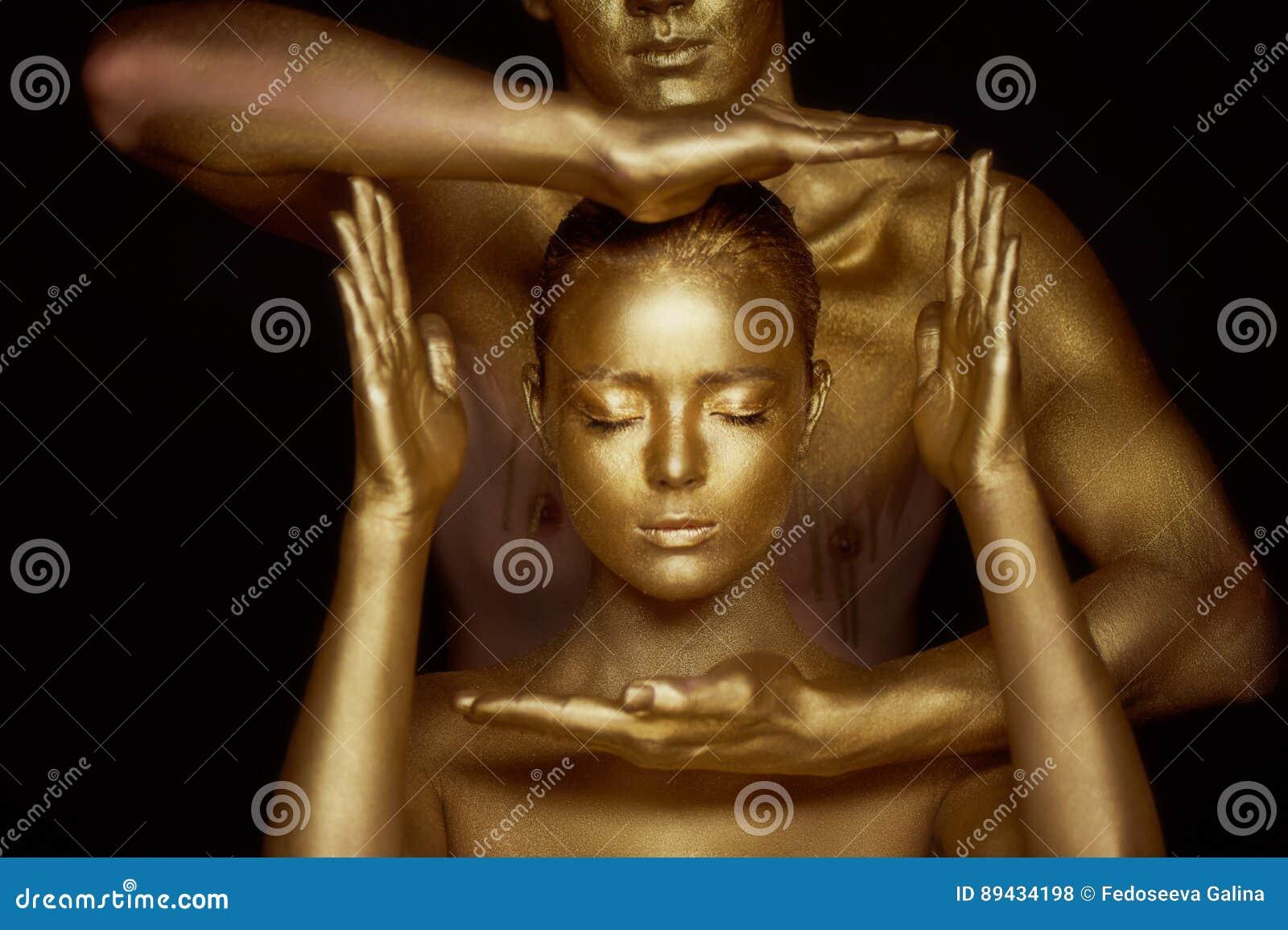 Um par de homens novos misteriosos, pintado na pintura do ouro A cara do ` s da menina é moldada por um quadro das mãos dos joven