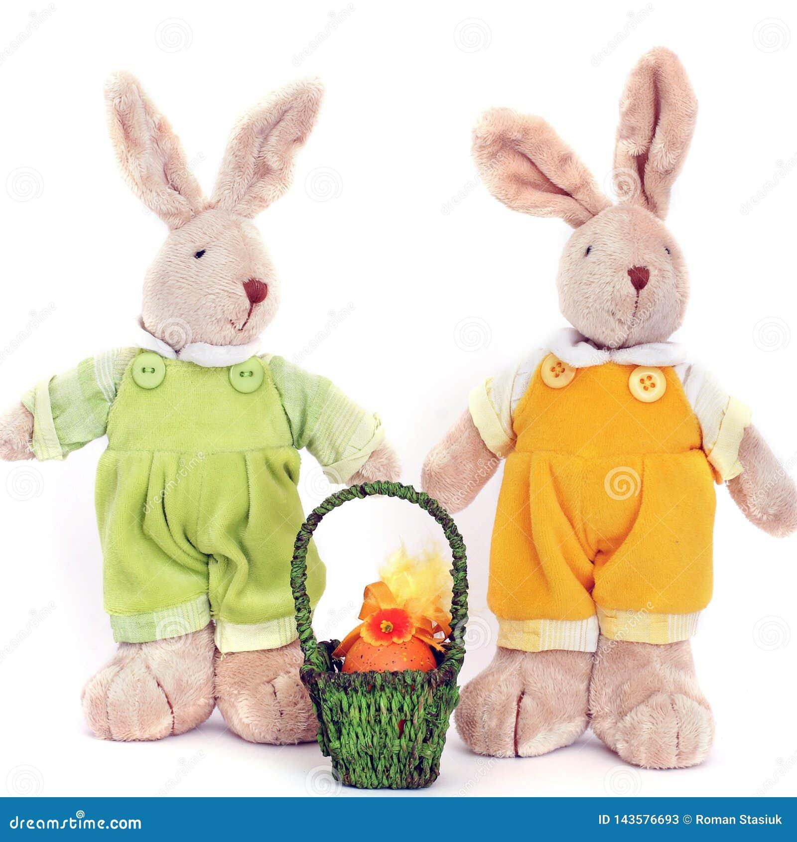 Um par de lebres macias do brinquedo bonito e de uma cesta dos ovos da páscoa