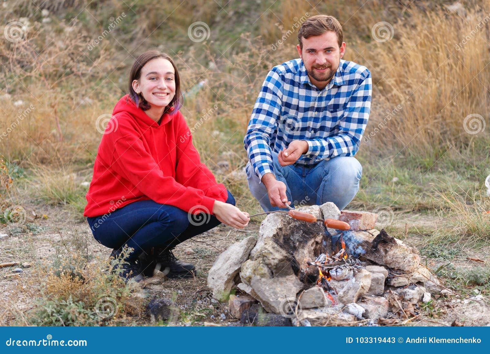 Um par em um piquenique frita salsichas apetitosas outdoors
