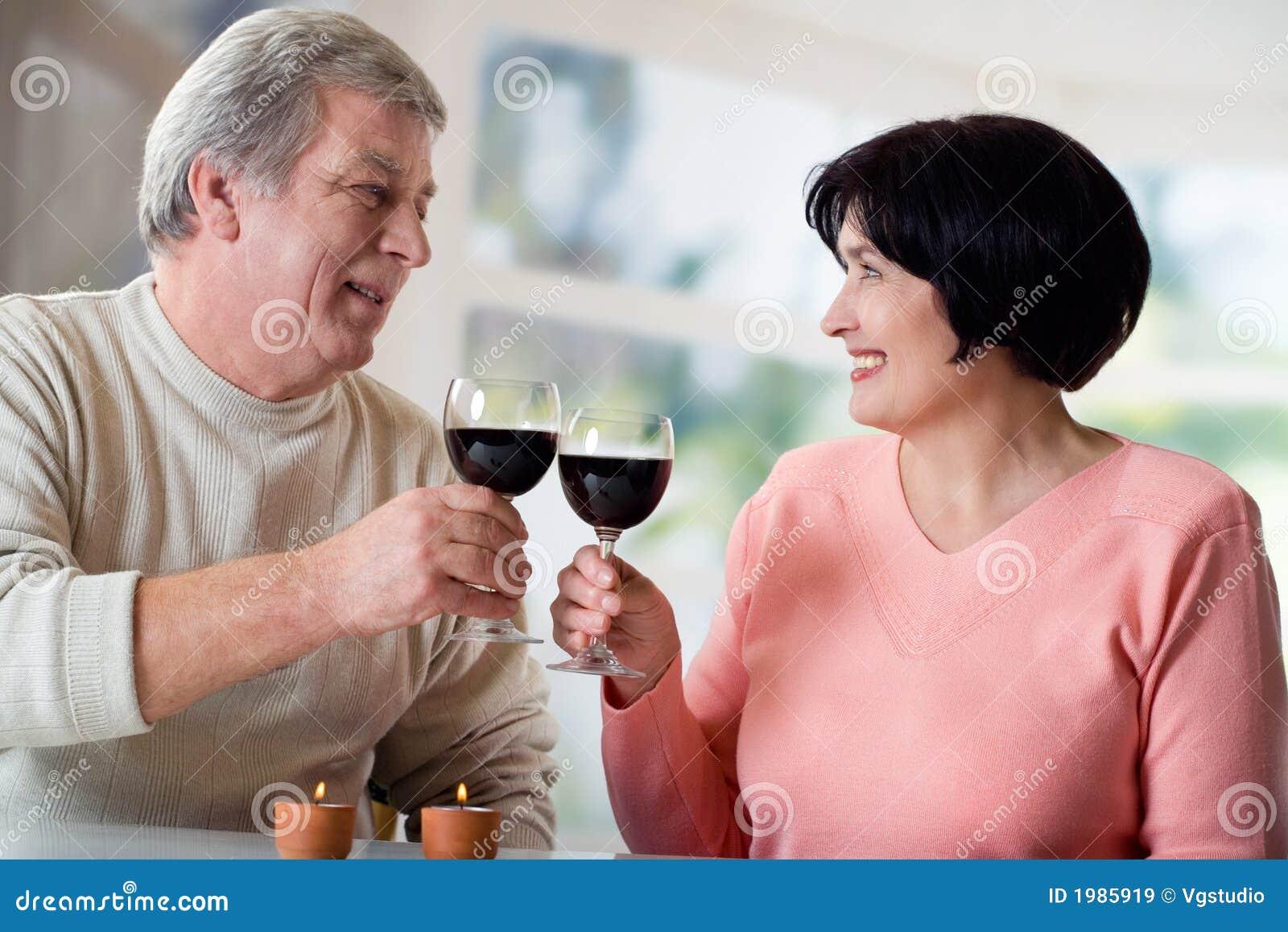 Um par idoso feliz que comemora o evento de vida junto com o vinho