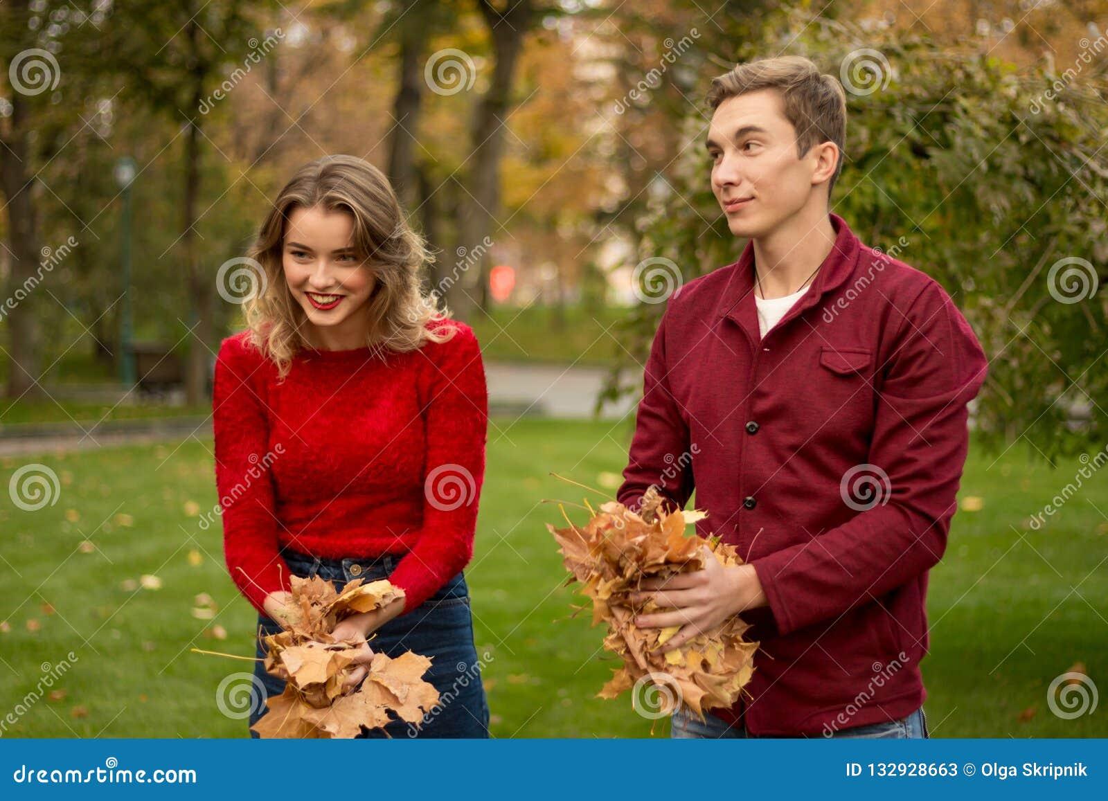 Um par joga acima as folhas amarelas, bordo, acima, enganando ao redor, outono data Rindo e tendo o divertimento