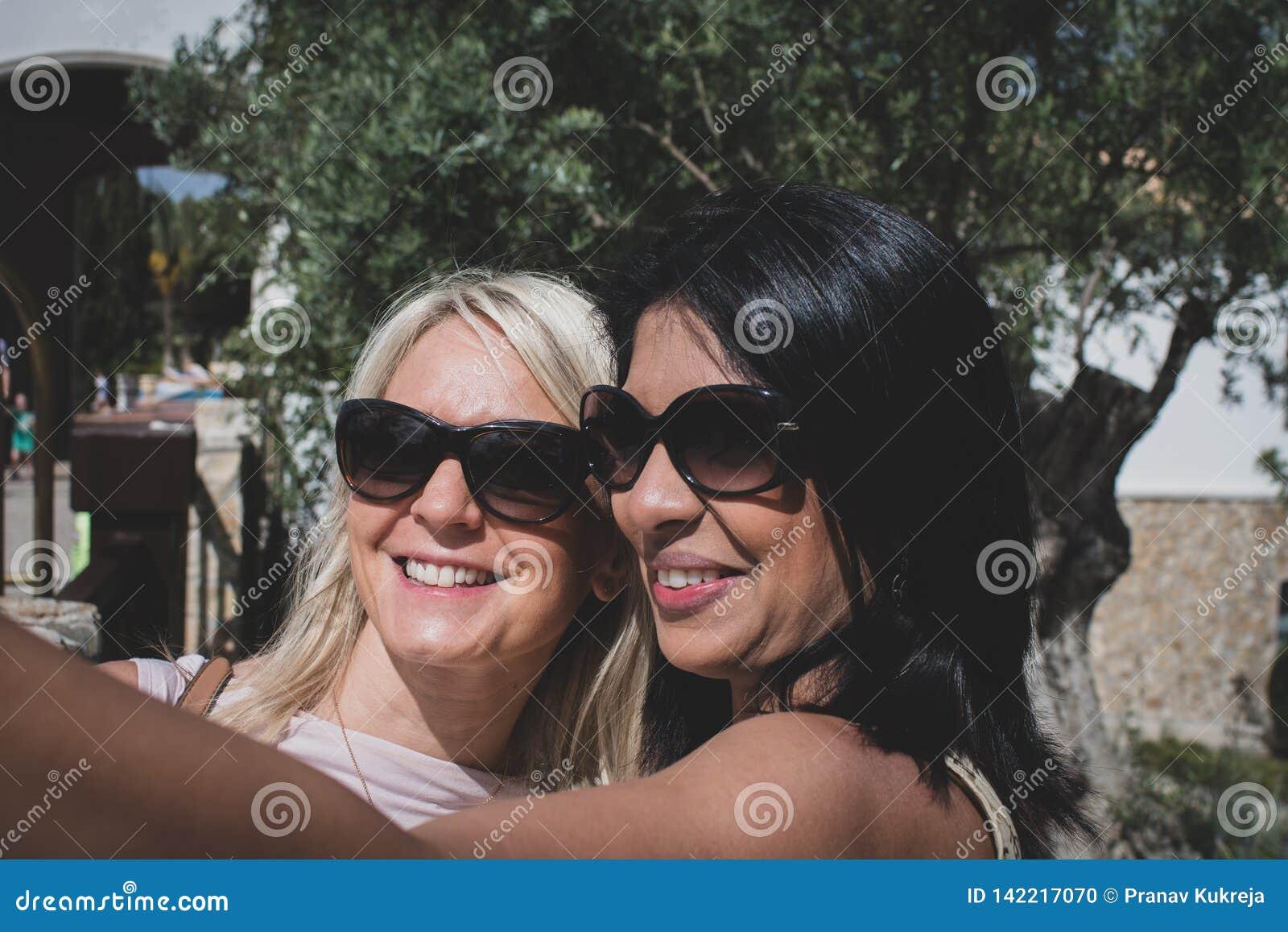 Um par lésbica que toma um selfie e um riso