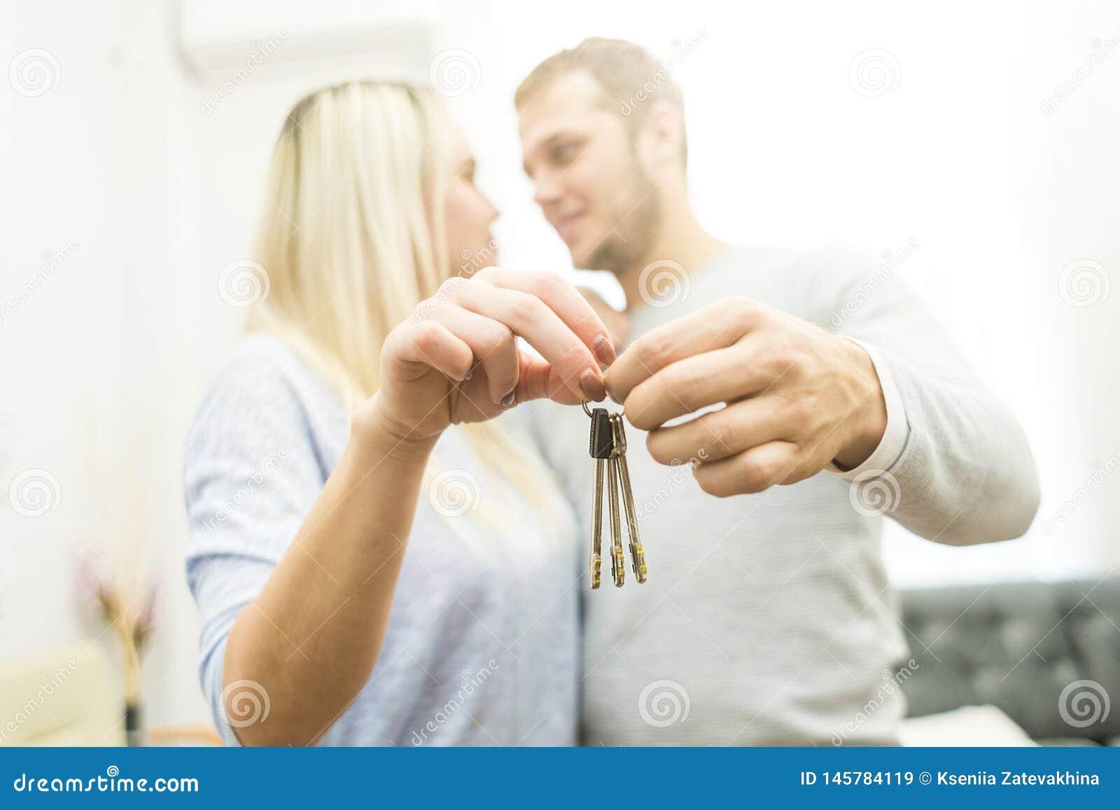 Um par novo bonito guarda na frente deles as chaves a seu apartamento novo