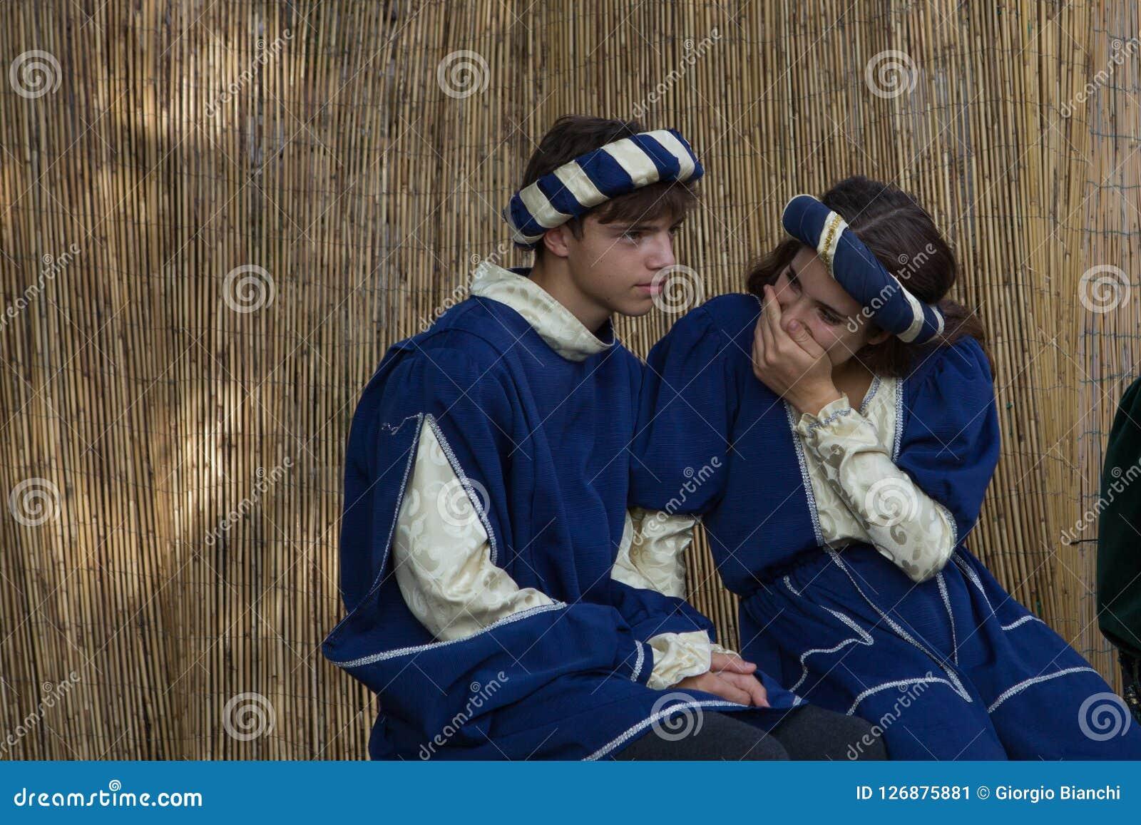 Um par novo de cortesões que têm o divertimento durante um banquete medieval