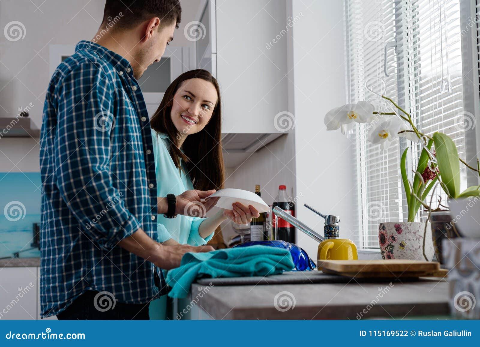 Um par novo na cozinha junto para lavar e limpar os pratos, uma vista inferior e uma vista lateral, a alegria da vida familiar