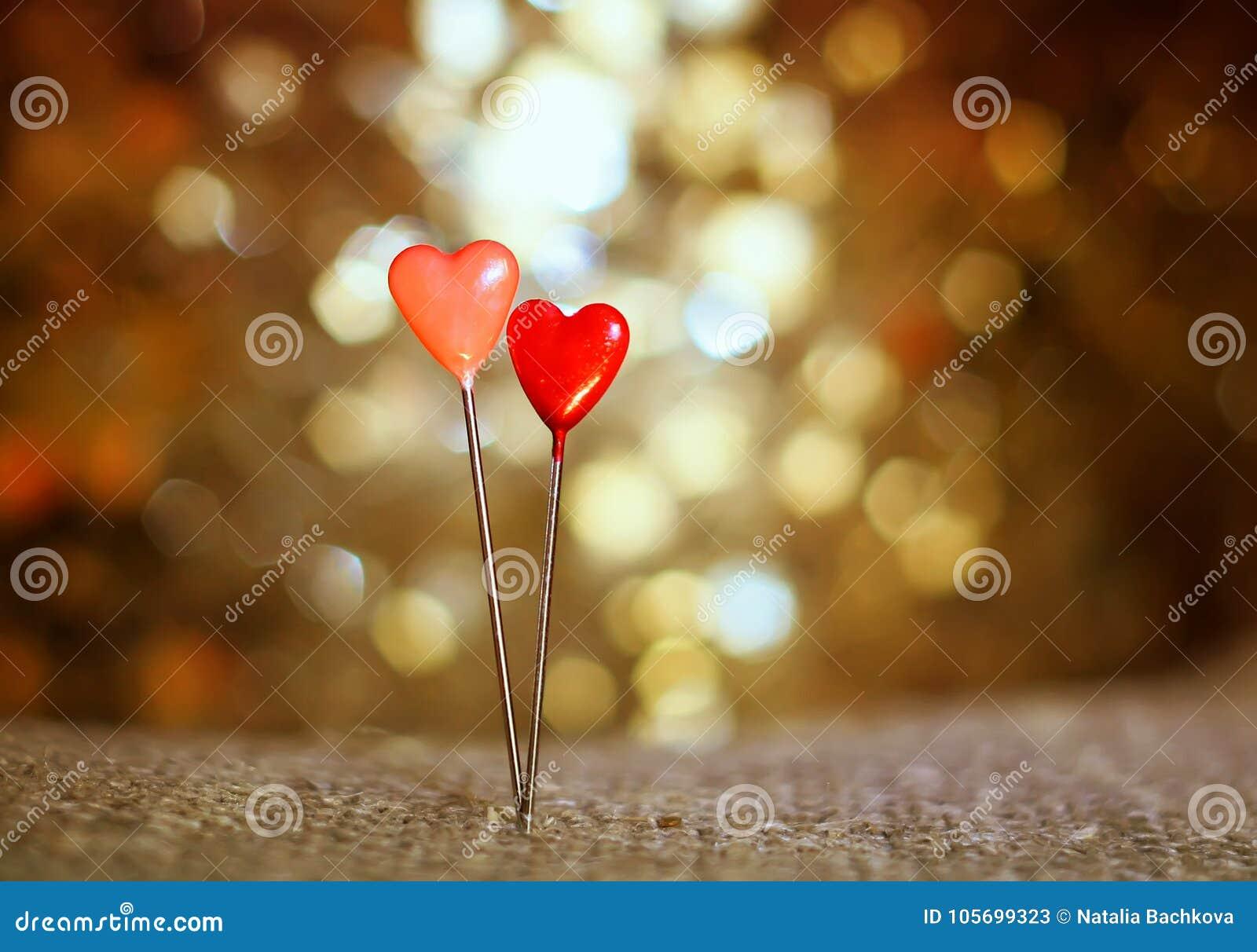 Um par pinos sob a forma dos corações vermelhos colaram na serapilheira o