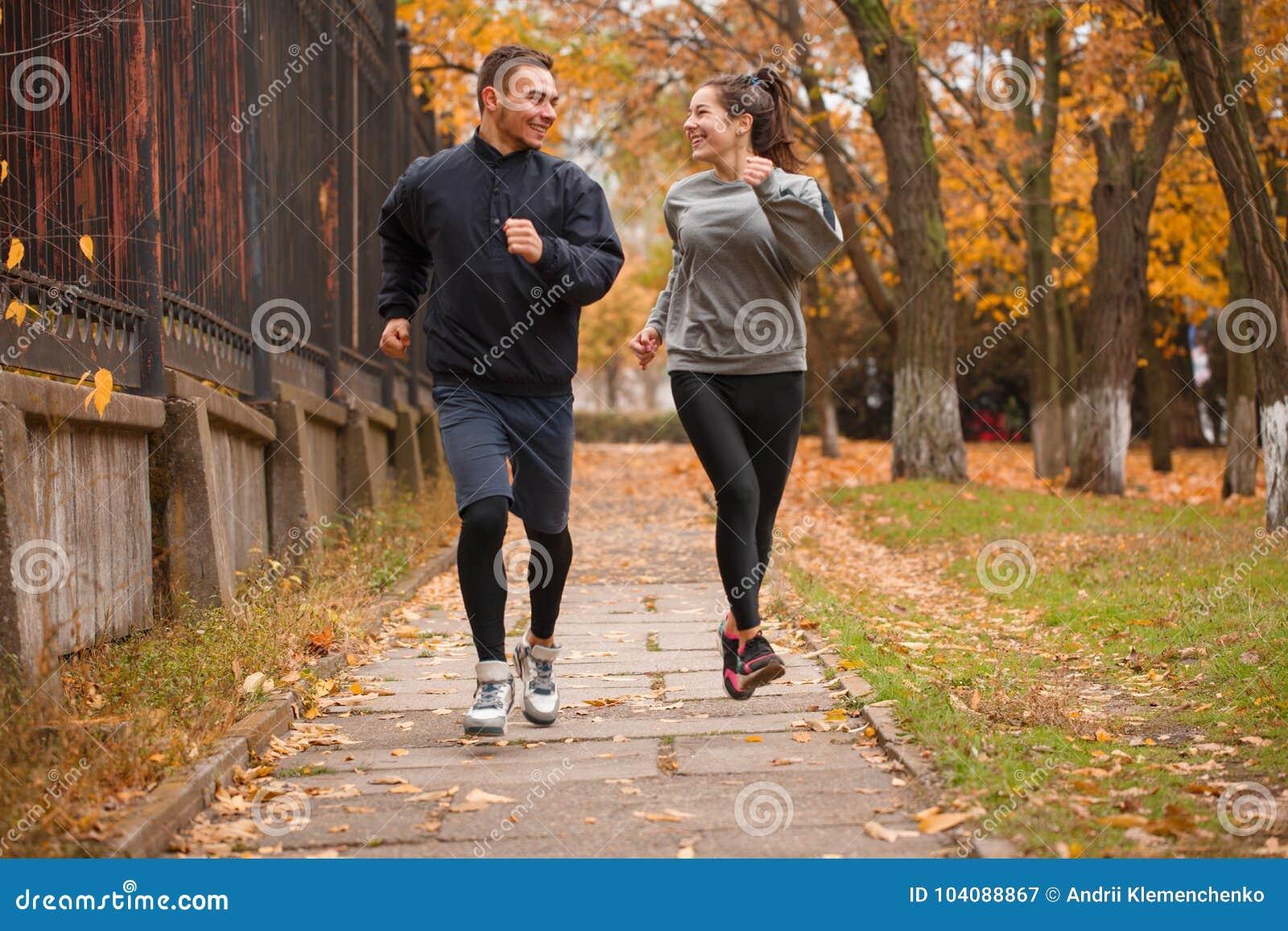 Um par que joga os esportes que correm no parque do outono outdoors