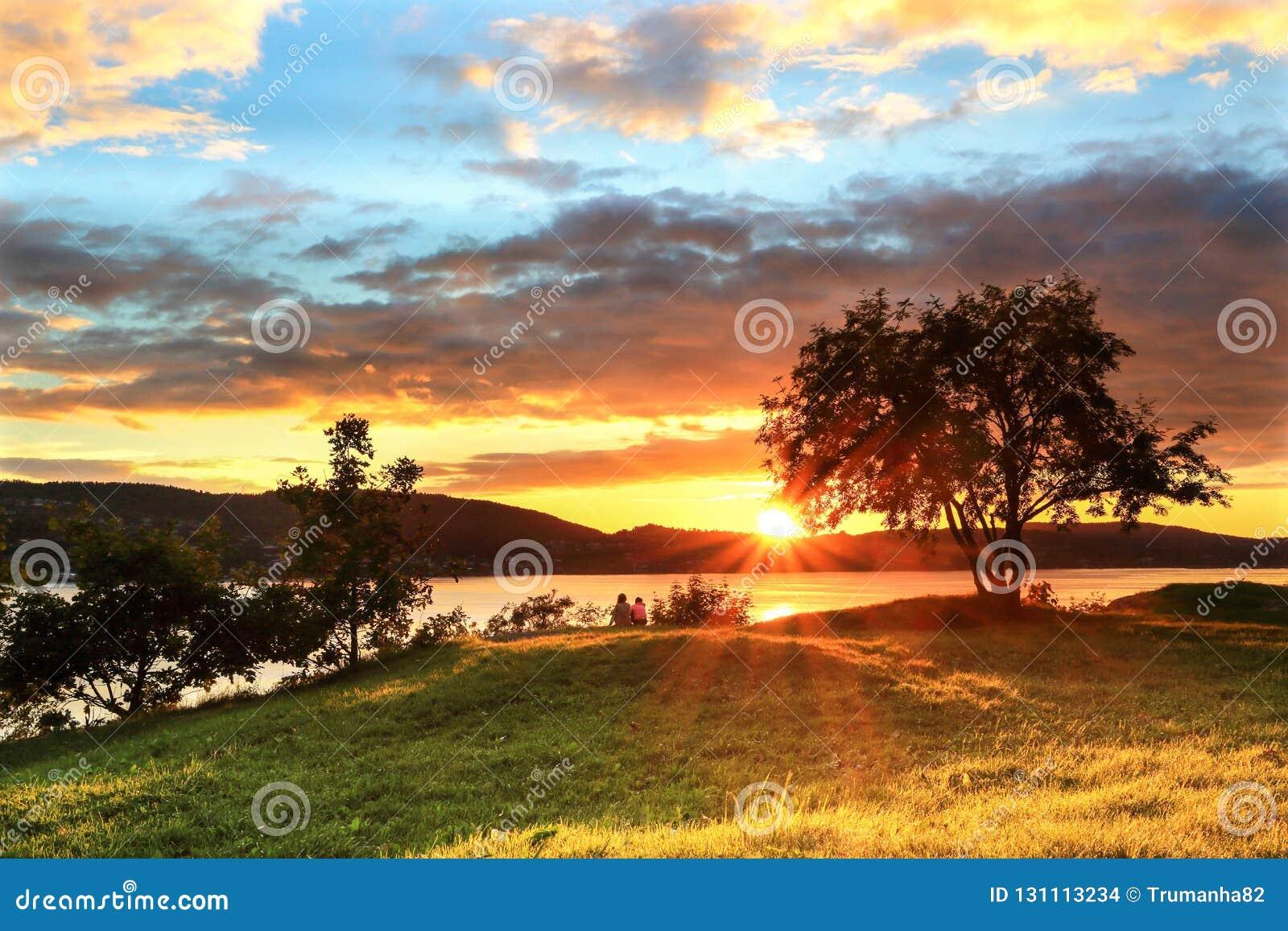 Um par que senta-se pelo fiorde no por do sol colorido em Bergen