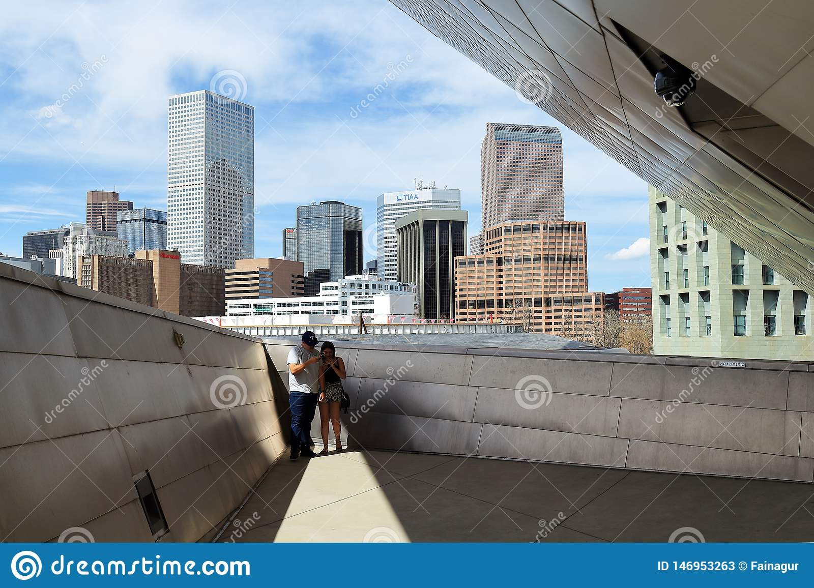 Um par que toma imagens na plataforma com uma vista na arquitetura da cidade do centro de Denver