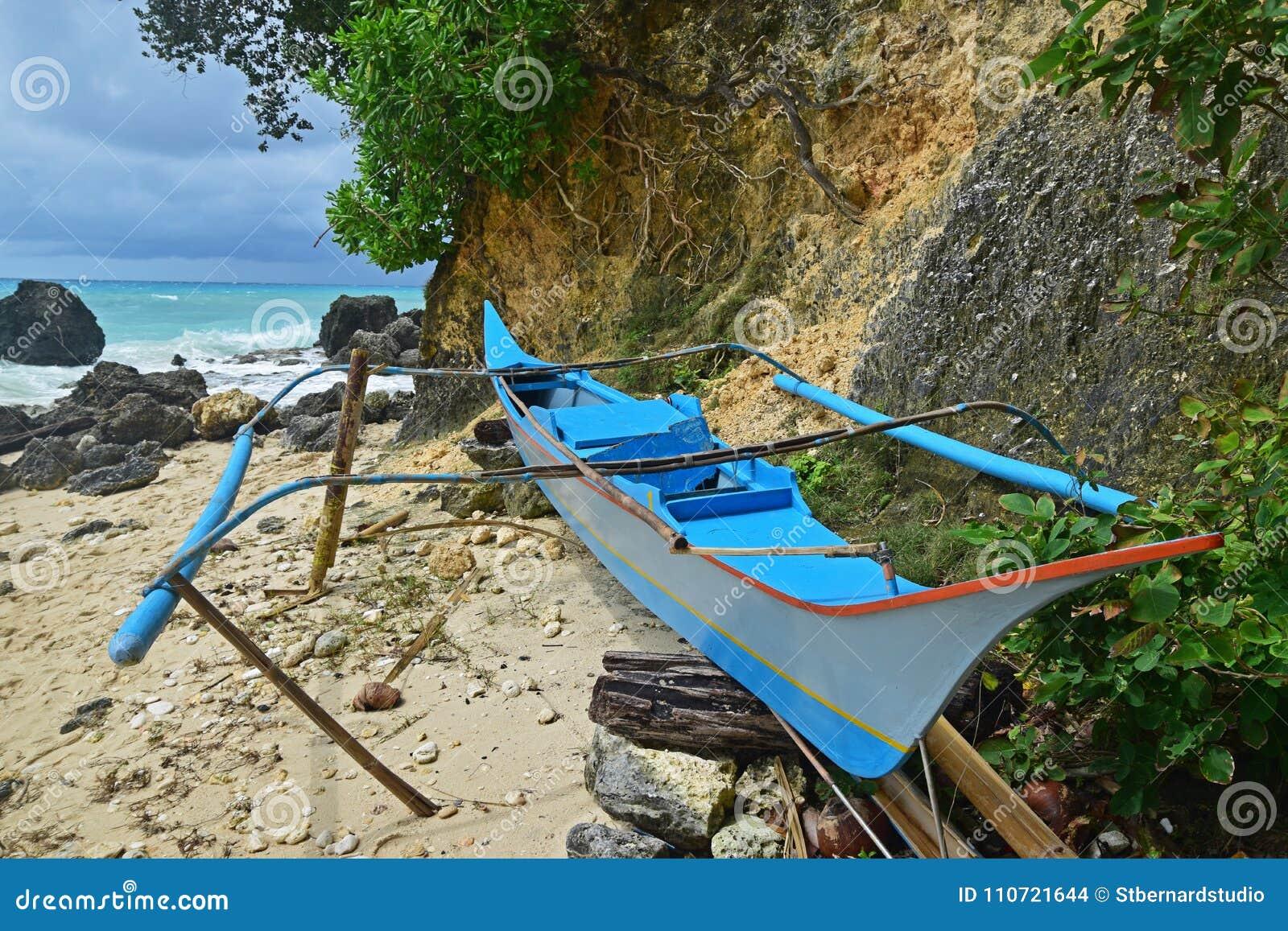 Um paraw azul tradicional da cor estacionou na praia na ilha de Boracay