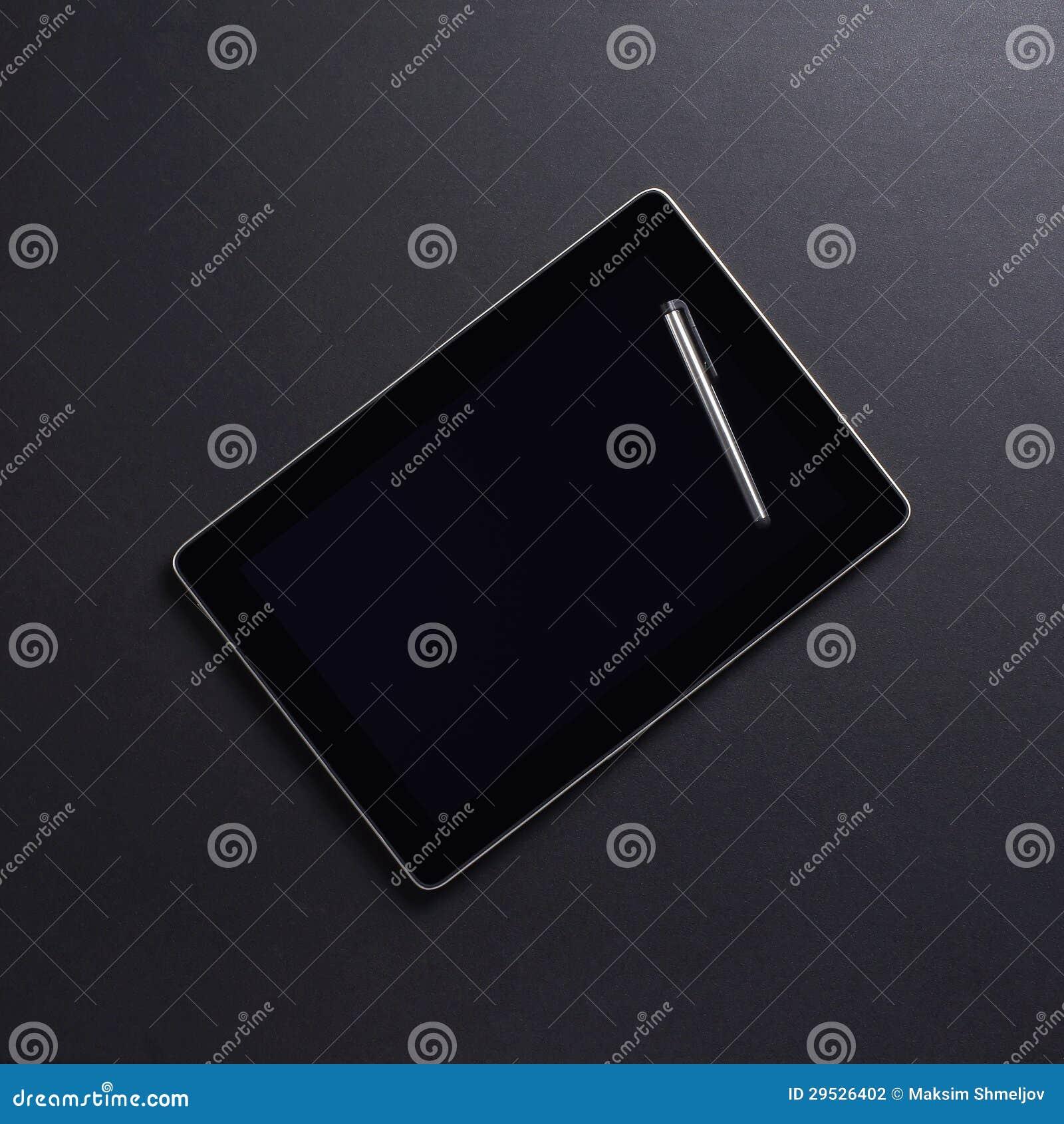 Um PC preto moderno da tabuleta e uma pena no preto