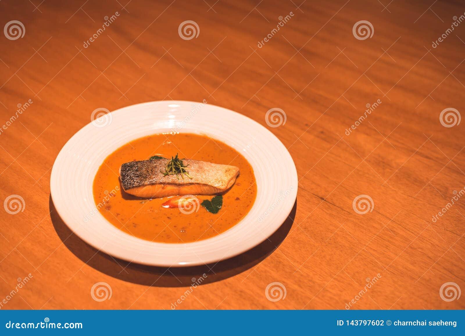Um peixe dos salmões com caril no prato no jantar da tabela
