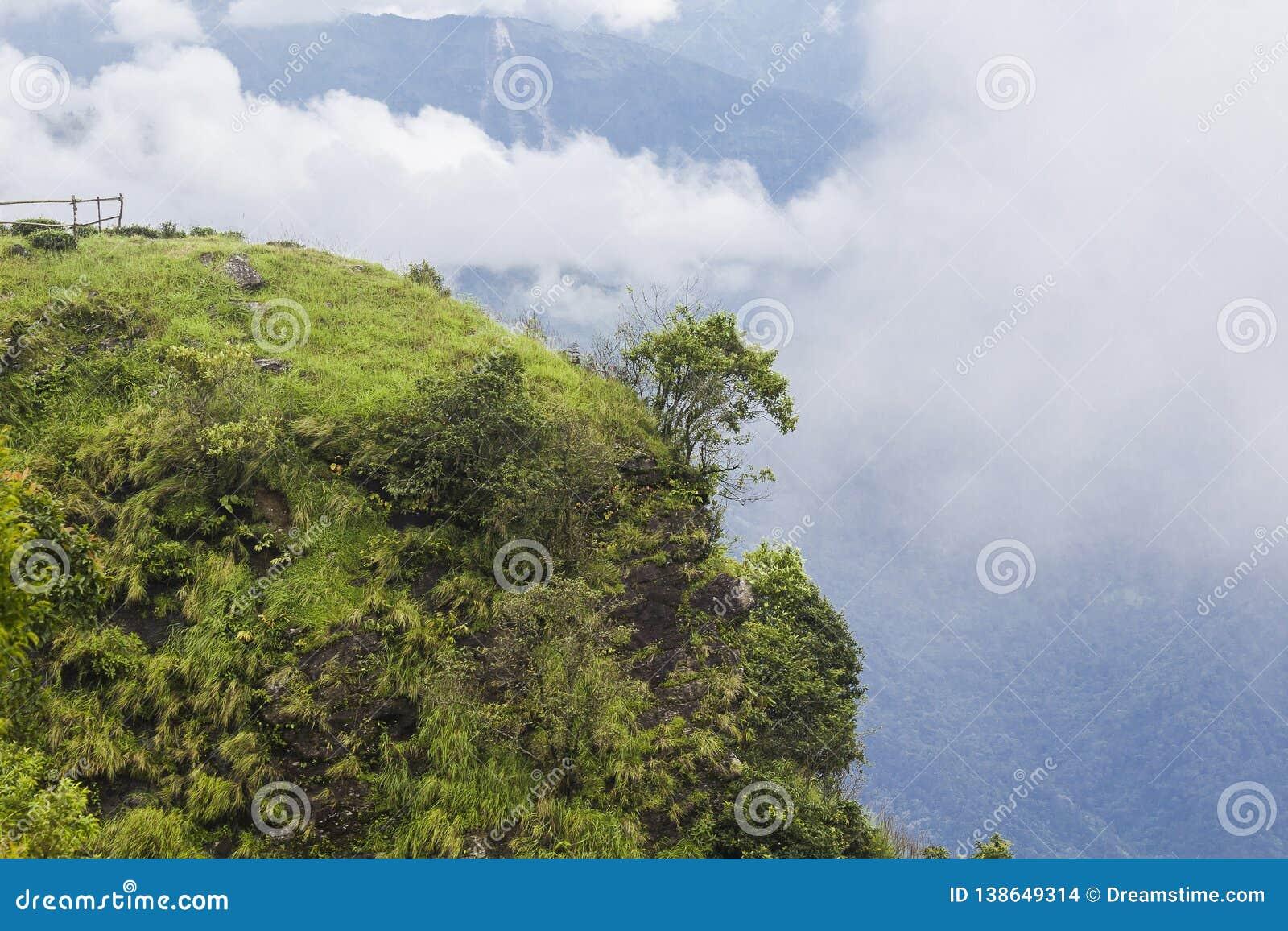 Um penhasco montanhoso verde com céu nebuloso