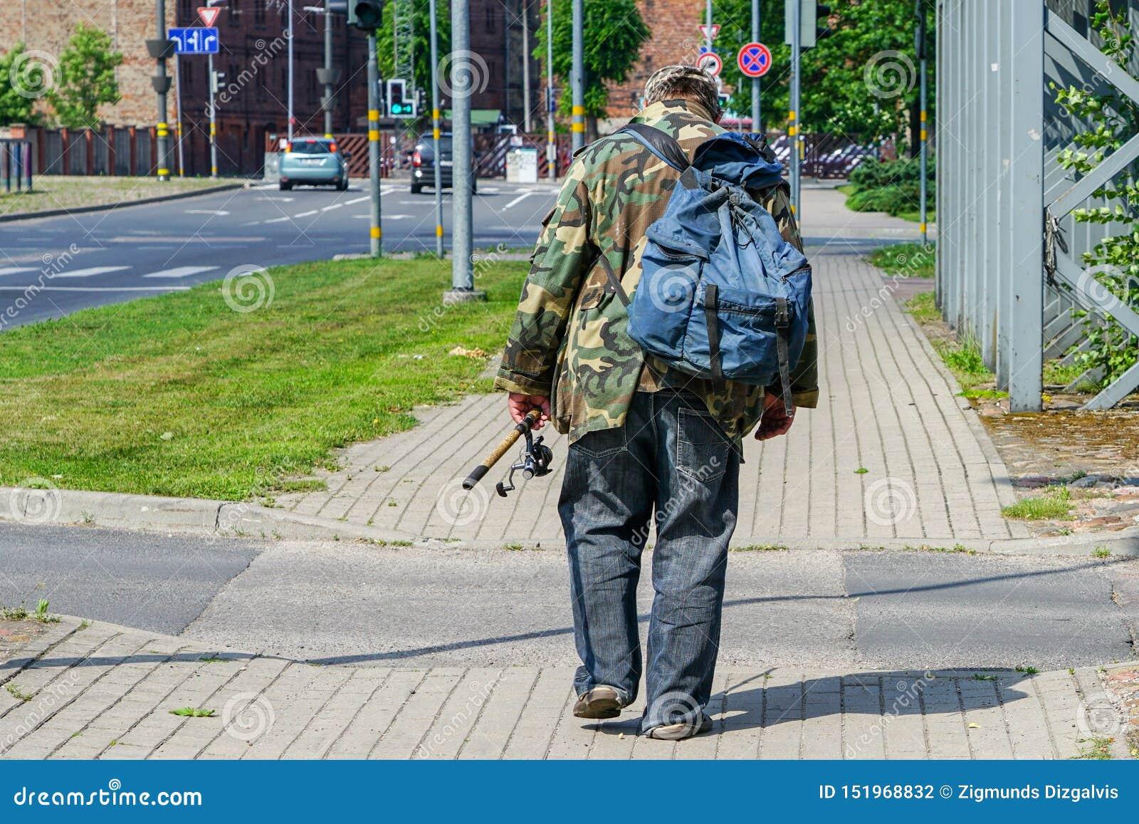 Um pescador bêbado com uma trouxa e uma vara de pesca em sua mão vai abaixo da rua da cidade