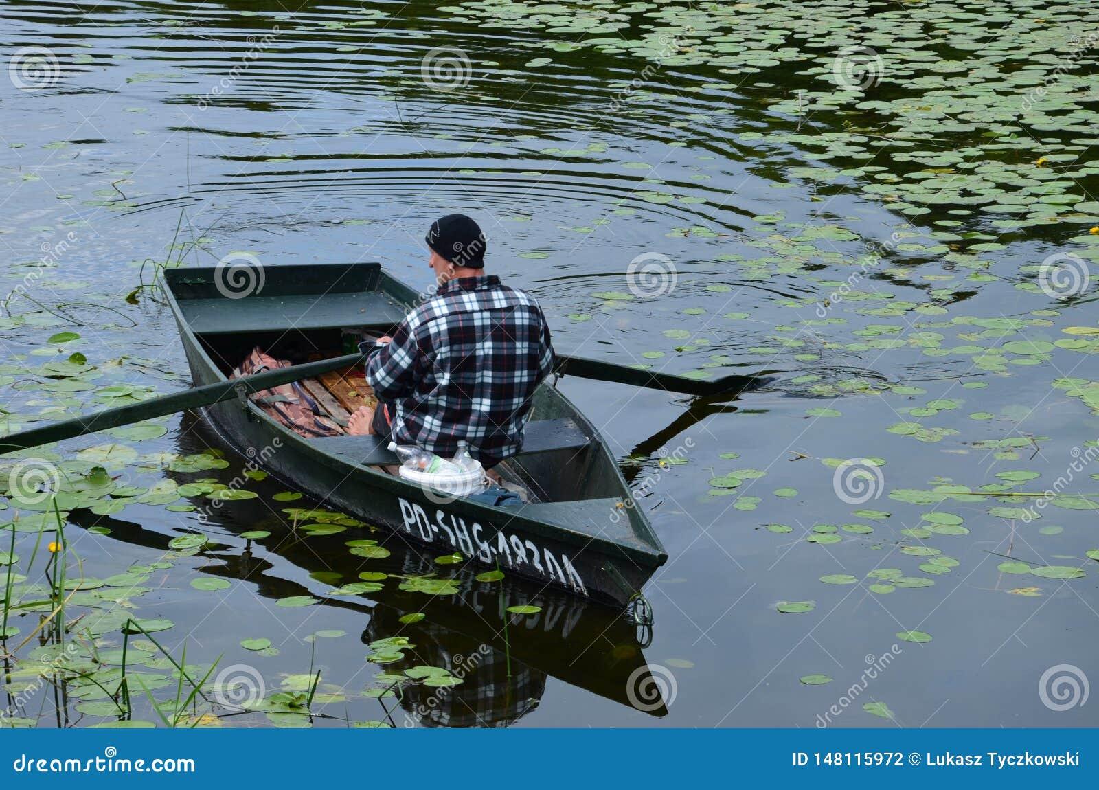 Um pescador em seu barco no lago no Polônia