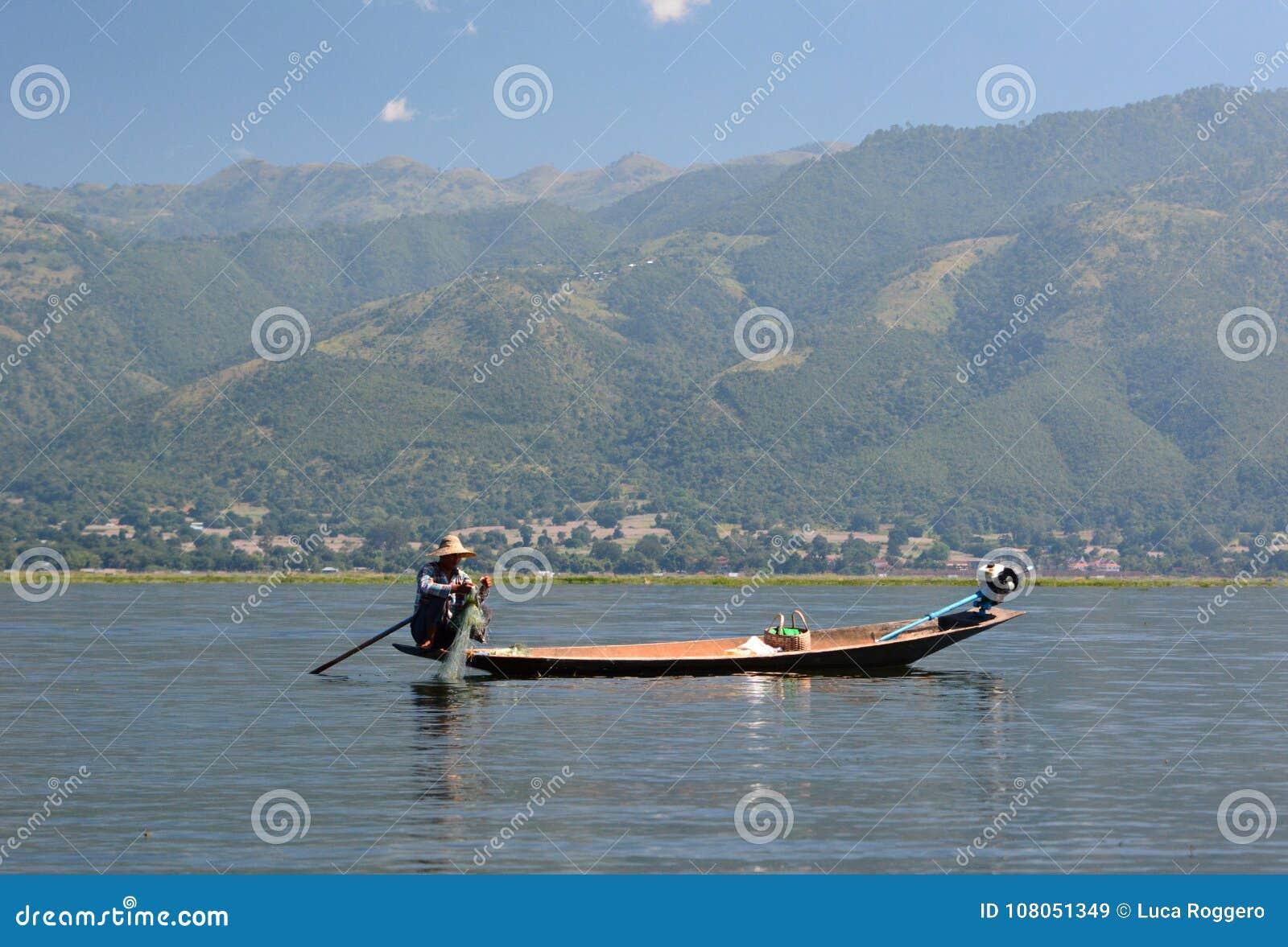 Um pescador em seu barco tradicional Lago Inle myanmar