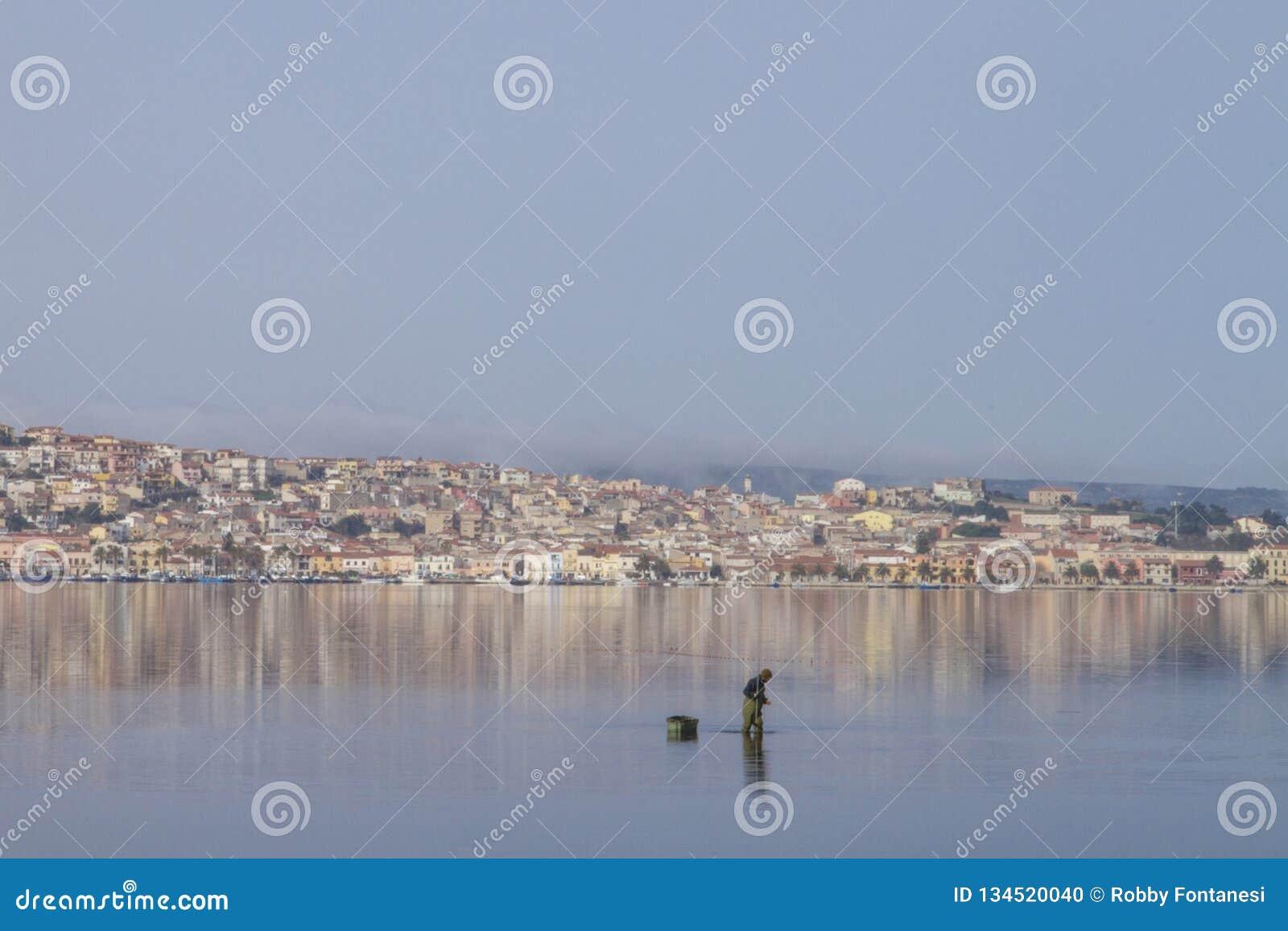 Um pescador no trabalho que dobra-se na água do mar lisa que reflete as casas de Sant 'Antioco em Sardinia