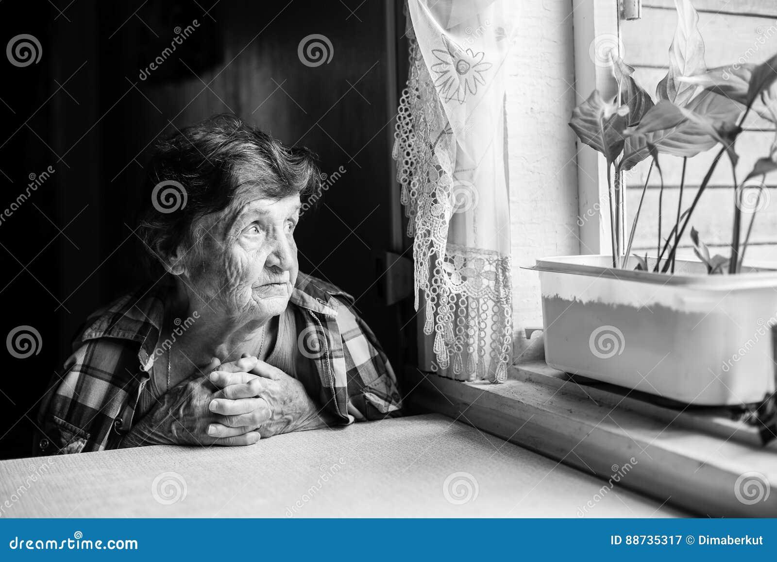 Um pining idoso da mulher na janela