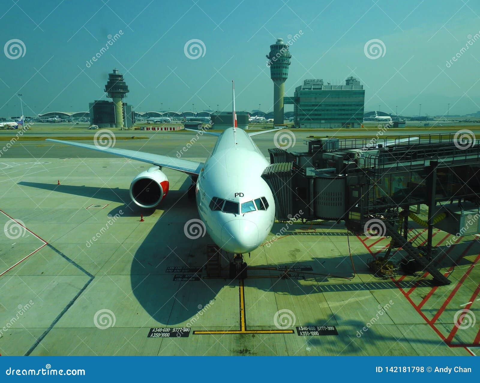 Um plano estacionado no passageiro de espera de HKIA para embarcar