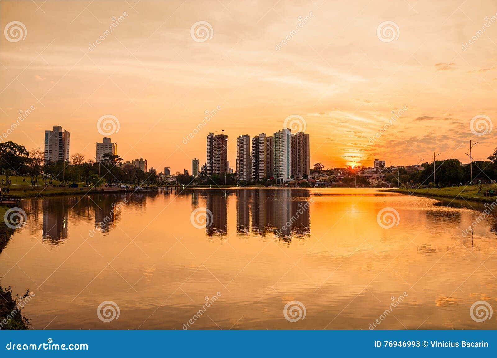 Um por do sol morno bonito no lago com construções e o fundo da cidade Cena refletida na água