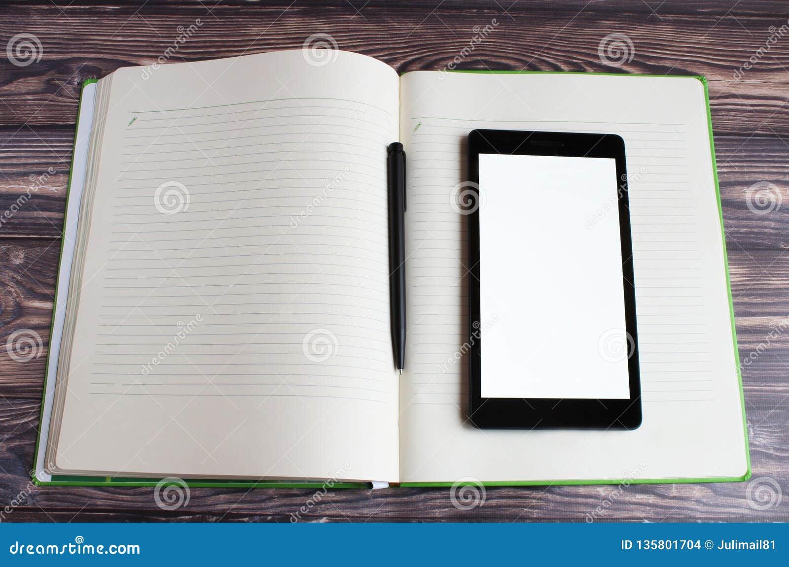 Um portátil preto encontra-se no grande caderno aberto No centro do caderno é uma pena preta para escrever